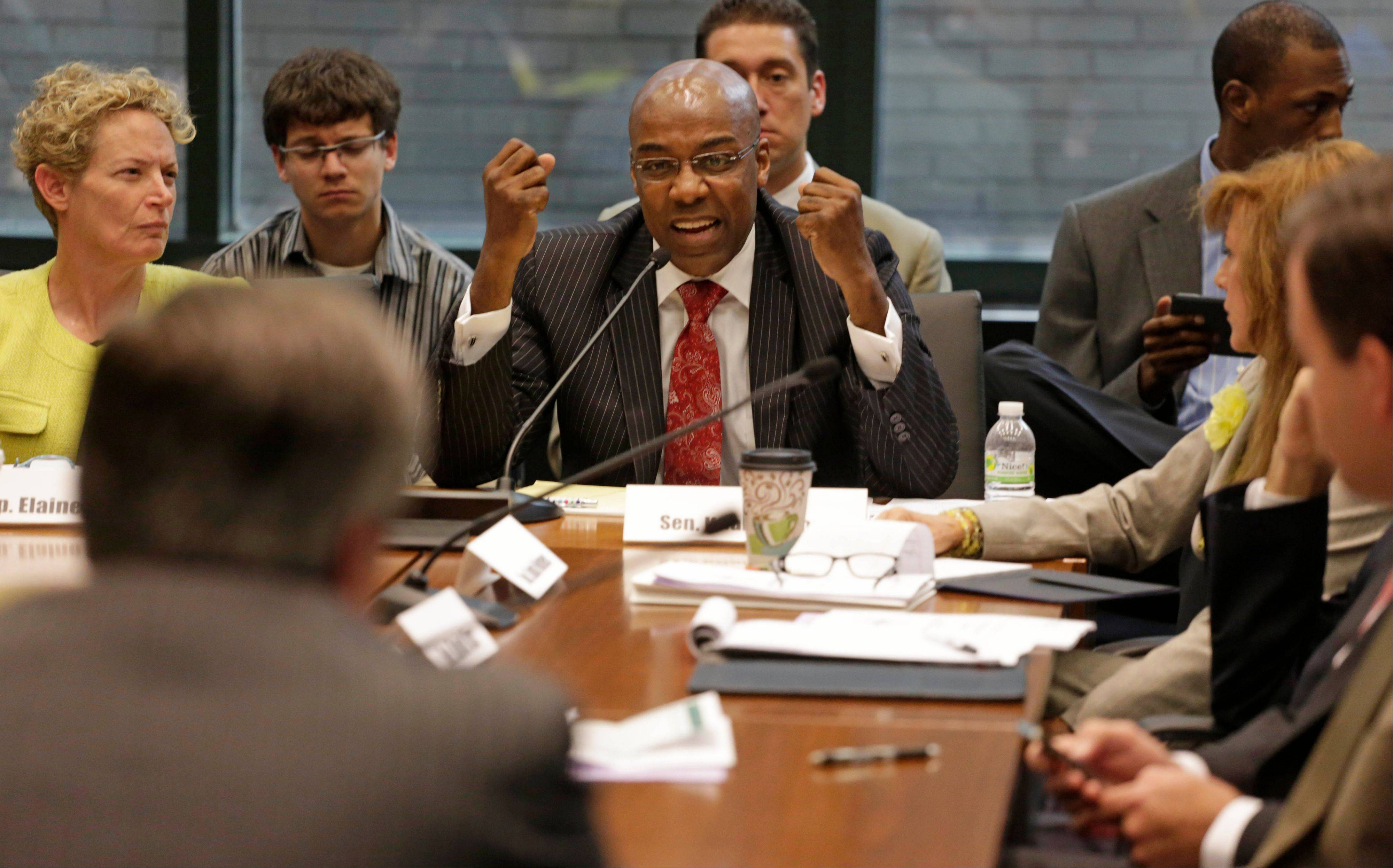 Pensions Conference Committee Chairman State Sen. Kwame Raoul, right and State Rep. Elaine Nekritz, left, join members of a bipartisan committee of Illinois lawmakers in questioning Ty Fahner, head of the Civic Committee of the Commercial Club of Chicago, during its first public pension hearing Thursday.