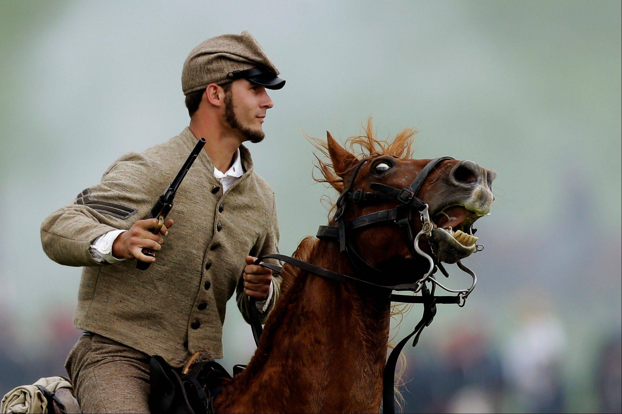 A mounted Confederate re-enactor takes part in a demonstration of a battle during ongoing activities commemorating the 150th anniversary of the Battle of Gettysburg on Friday at Bushey Farm in Gettysburg, Pa.