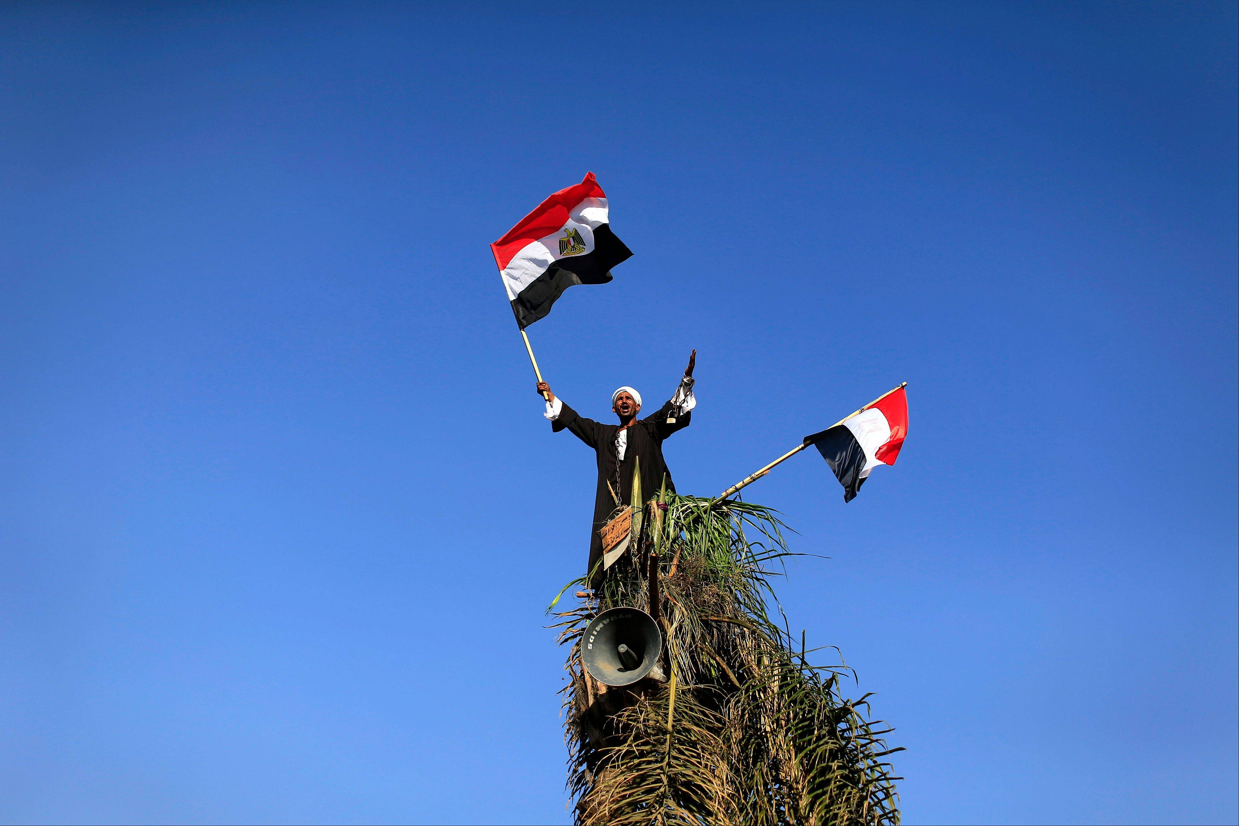 An opponent of Egypt�s Islamist President Mohammed Morsi waves Egyptian flags Friday during a protest outside the defense ministry, in Cairo, Egypt.