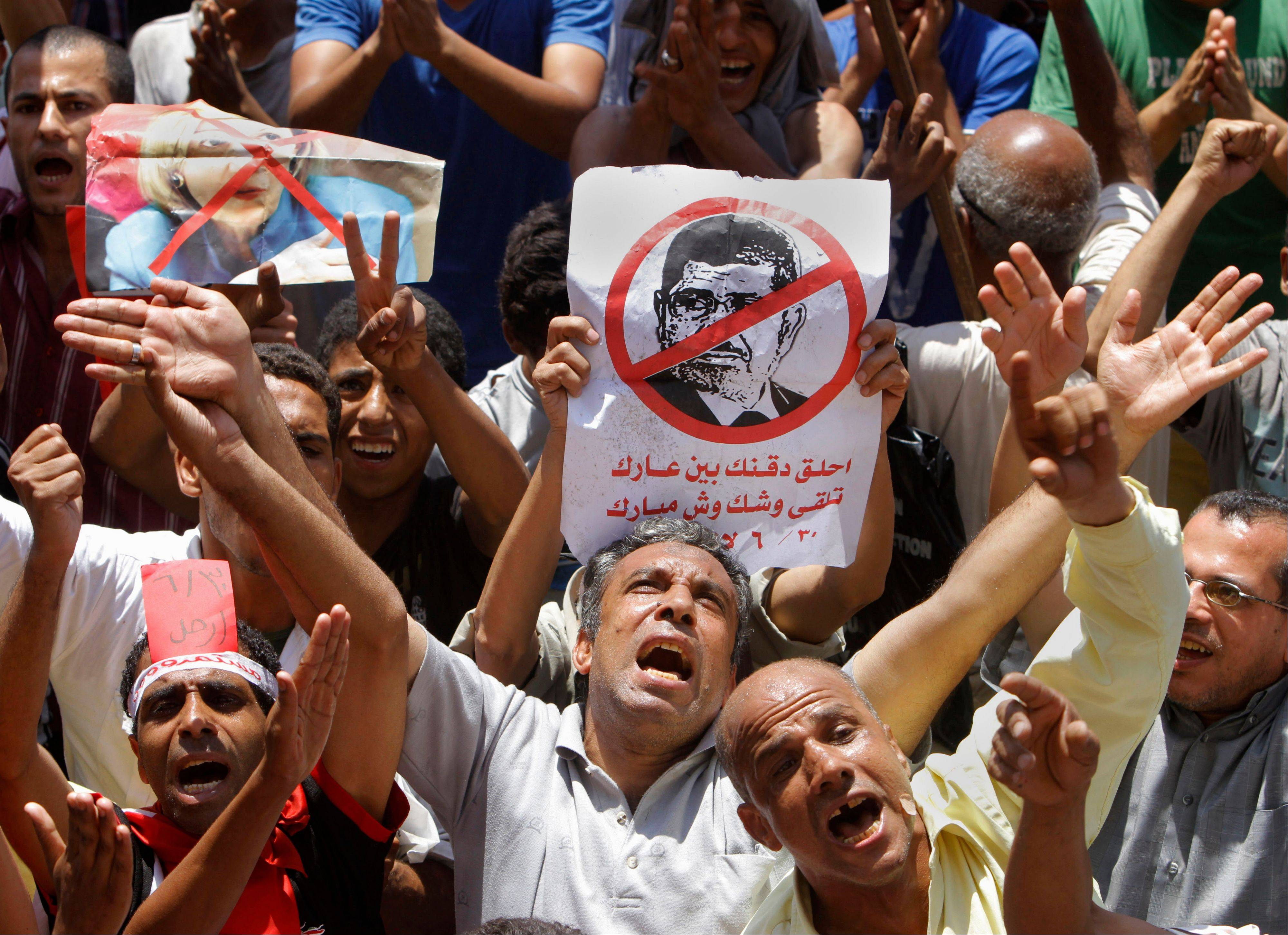 Egyptian protesters shout anti-Muslim Brotherhood slogans as they hold posters depicting U.S. Ambassador to Egypt Anne Patterson and President Mohammed Morsi during a protest in Tahrir Square, the focal point of Egyptian uprising, in Cairo, Egypt, Friday, June 28, 2013. Arabic on the poster at center reads, �shave your beard show your shame, you will look like Mubarak.� Egypt�s opposition plans to bring out massive crowds on Sunday in protests nationwide, vowing to force President Mohammed Morsi to step down.