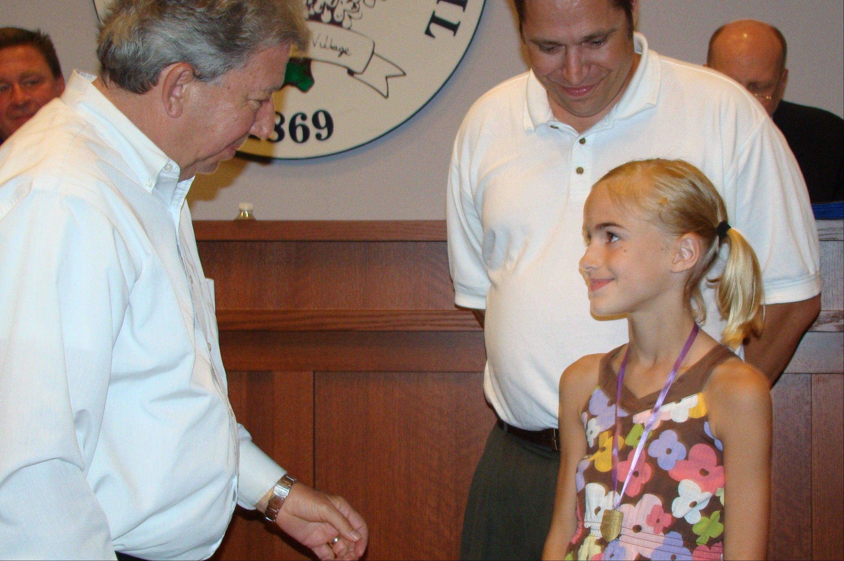Julia Pate, 8, with her father, Jay, receives a medal for good character from Lombard Trustee Dan Whittington.