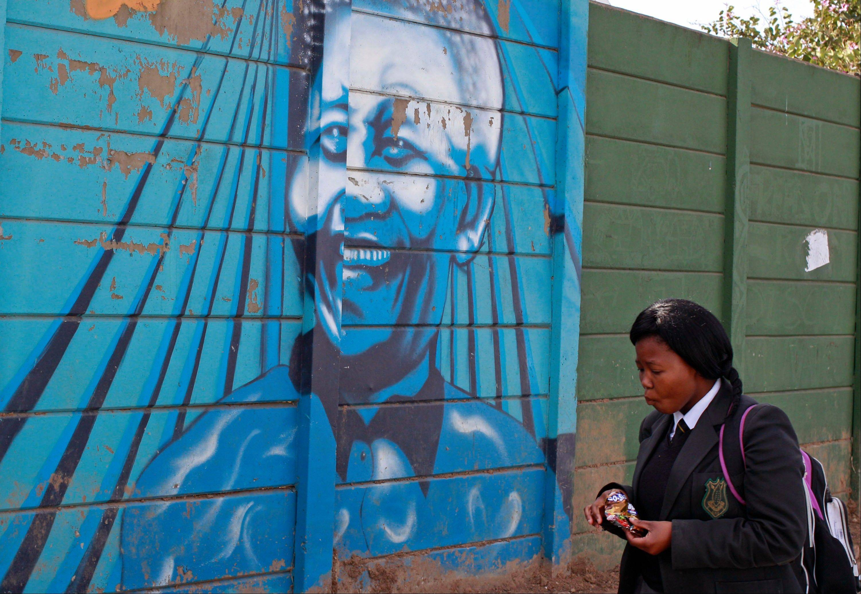 A schoolgirl walk past a mural of former South African President Nelson Mandela in the town of Umtata, South Africa, Friday, June 28, 2013. Members of Nelson Mandela�s family as well as South African Cabinet ministers have visited the hospital where the 94-year-old former president is critically ill.