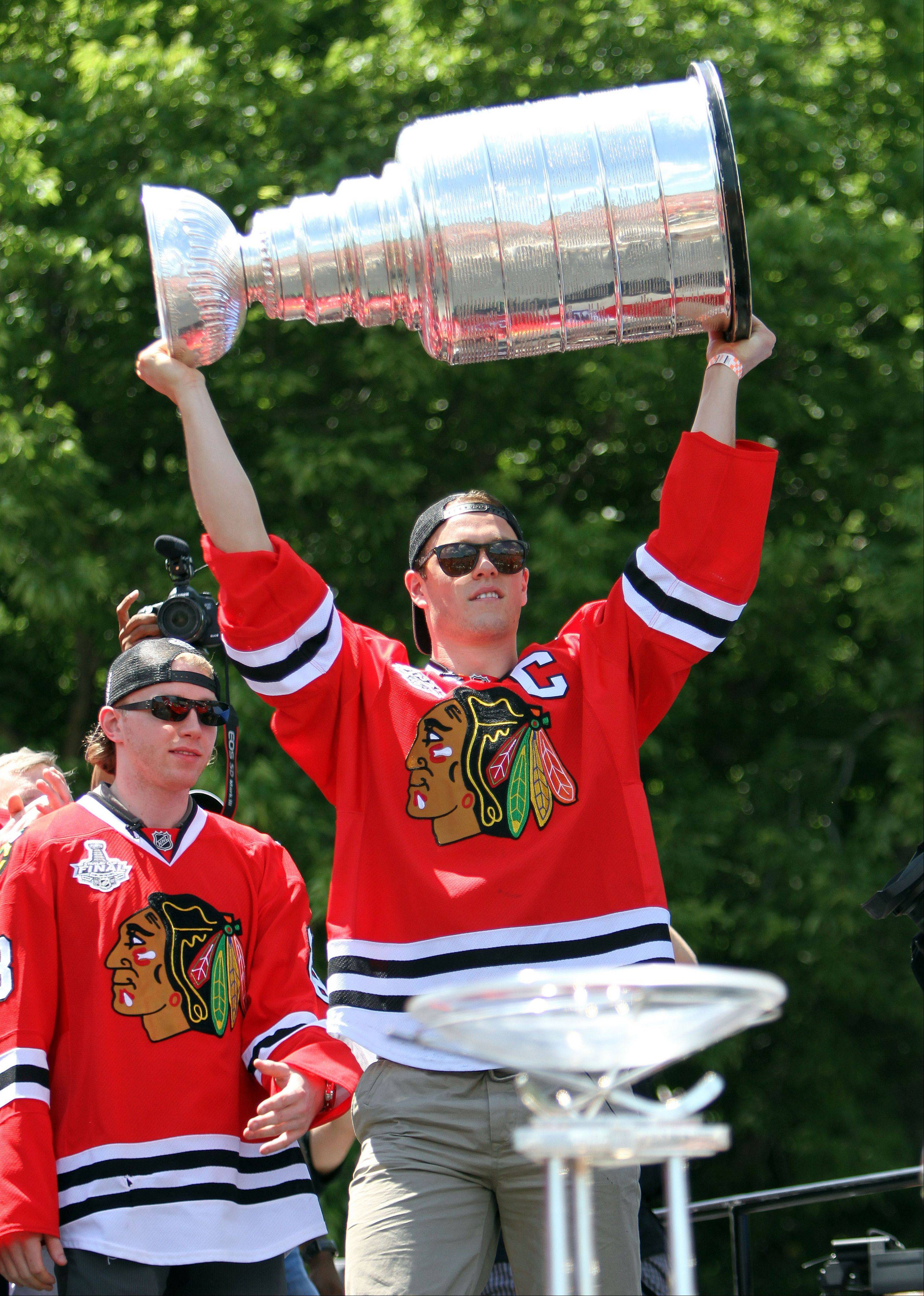 Steve Lundy/slundy@dailyherald.com Chicago Blackhawks center Jonathan Toews carries in the Stanley Cup during the Blackhawks Stanley Cup rally at Hutchinson Field in Chicago Friday morning.