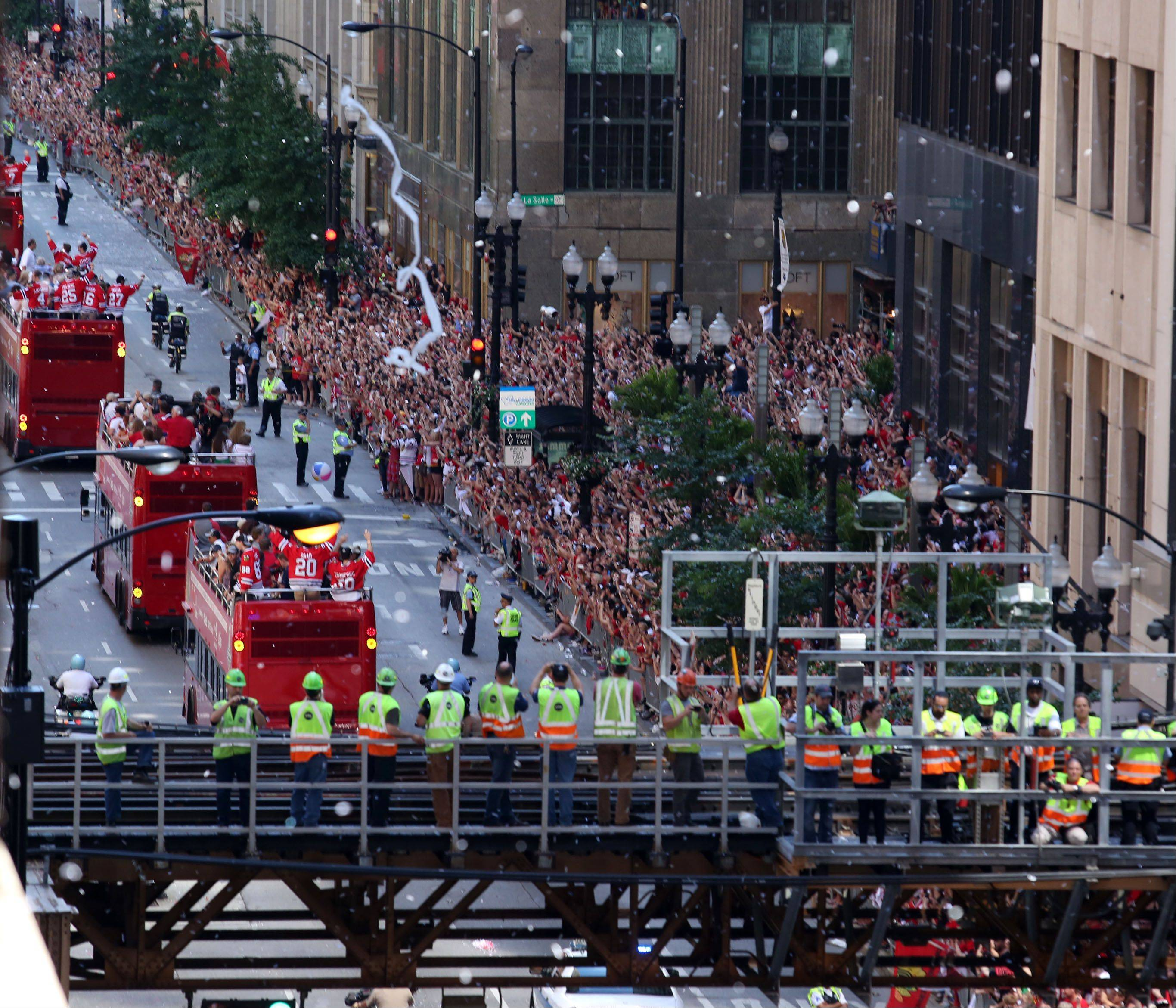 CTA workers get a high angle view from transit tracks of the Blackhawks parade traveling east on Washington Street in Chicago on Friday.