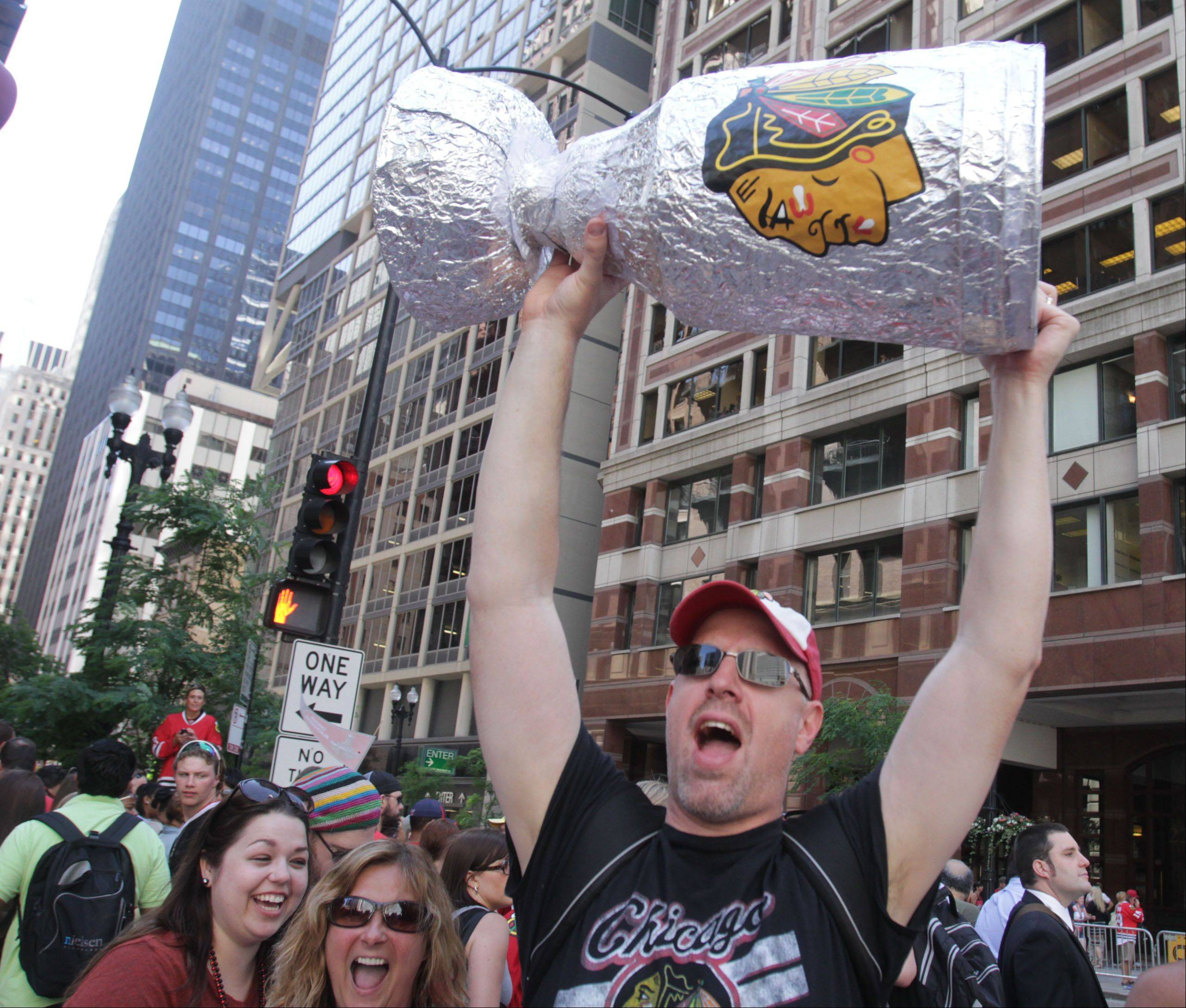 Kevin Quinn of Naperville lifts his homemade Stanley Cup as the Blackhawks parade travels past him on Washington Street in Chicago on Friday.