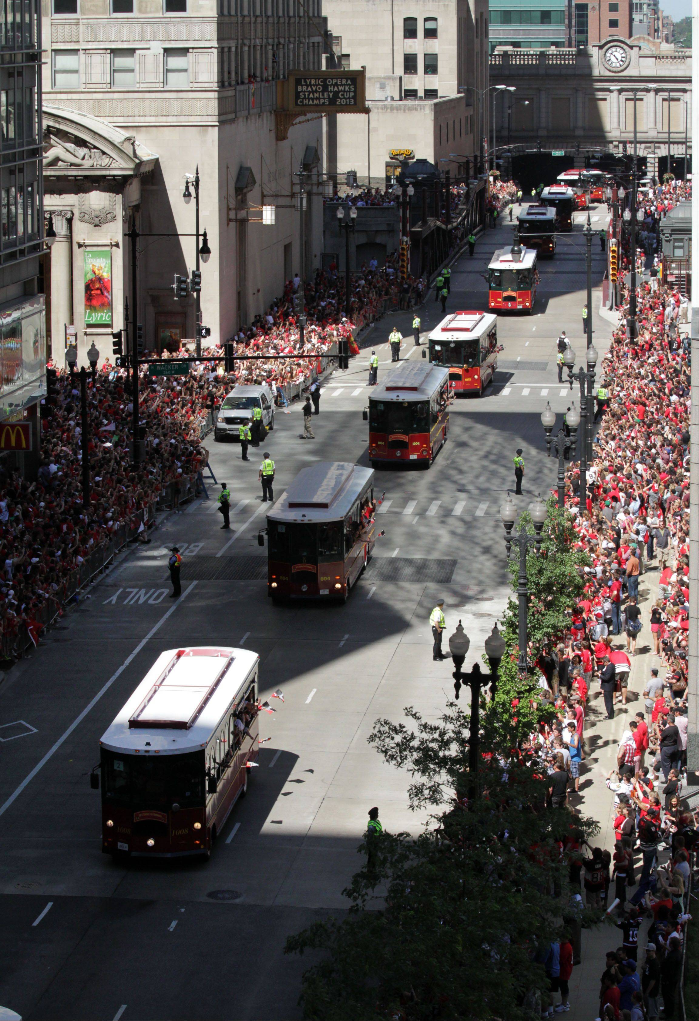 Trolleys carrying family members travel ahead of the Blackhawks parade on Washington Street in Chicago on Friday.