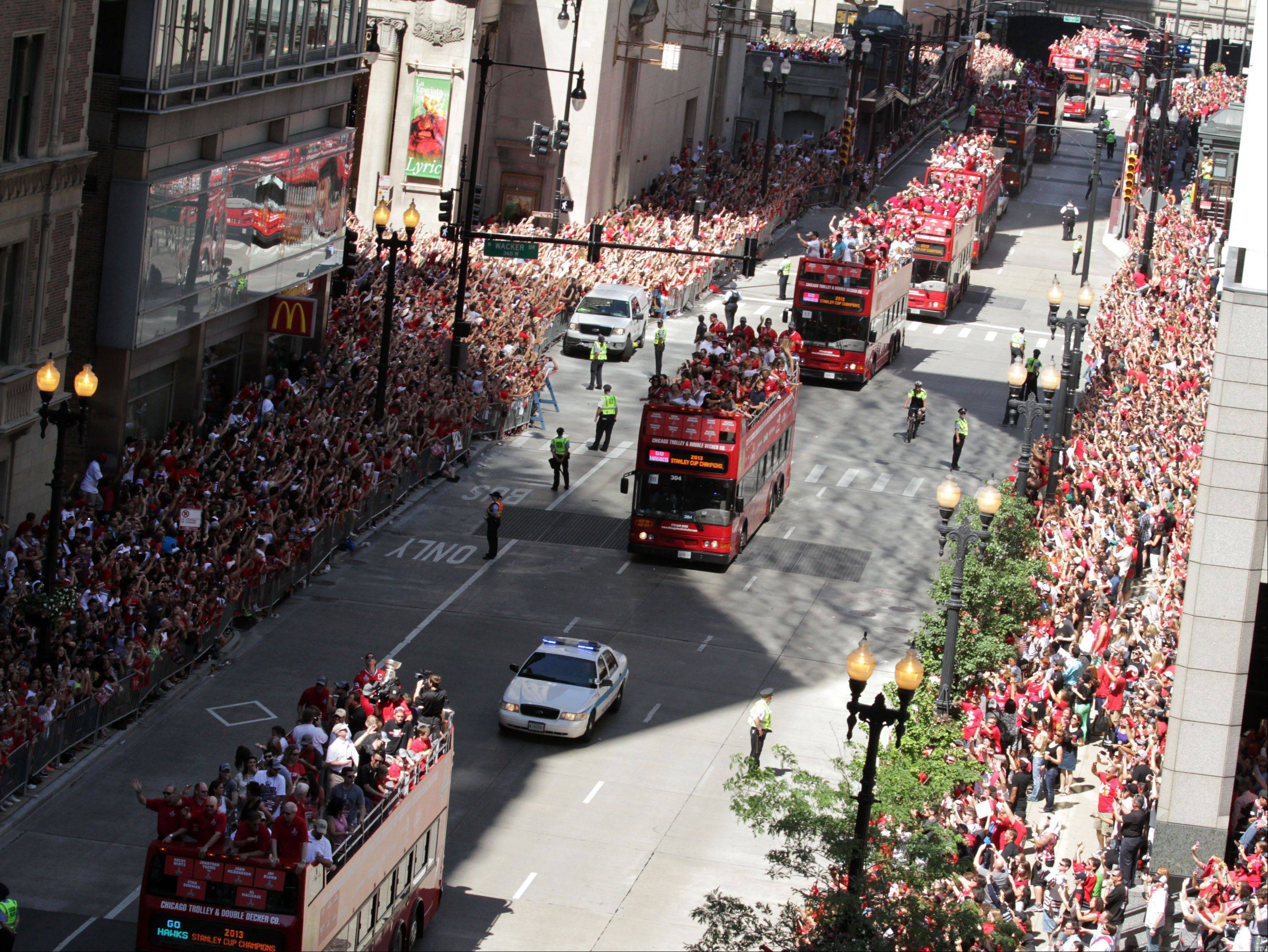 Double-decker buses carrying Blackhawks players and the Stanley Cup travel east on Washington Street to Michigan Avenue in Chicago on Friday.