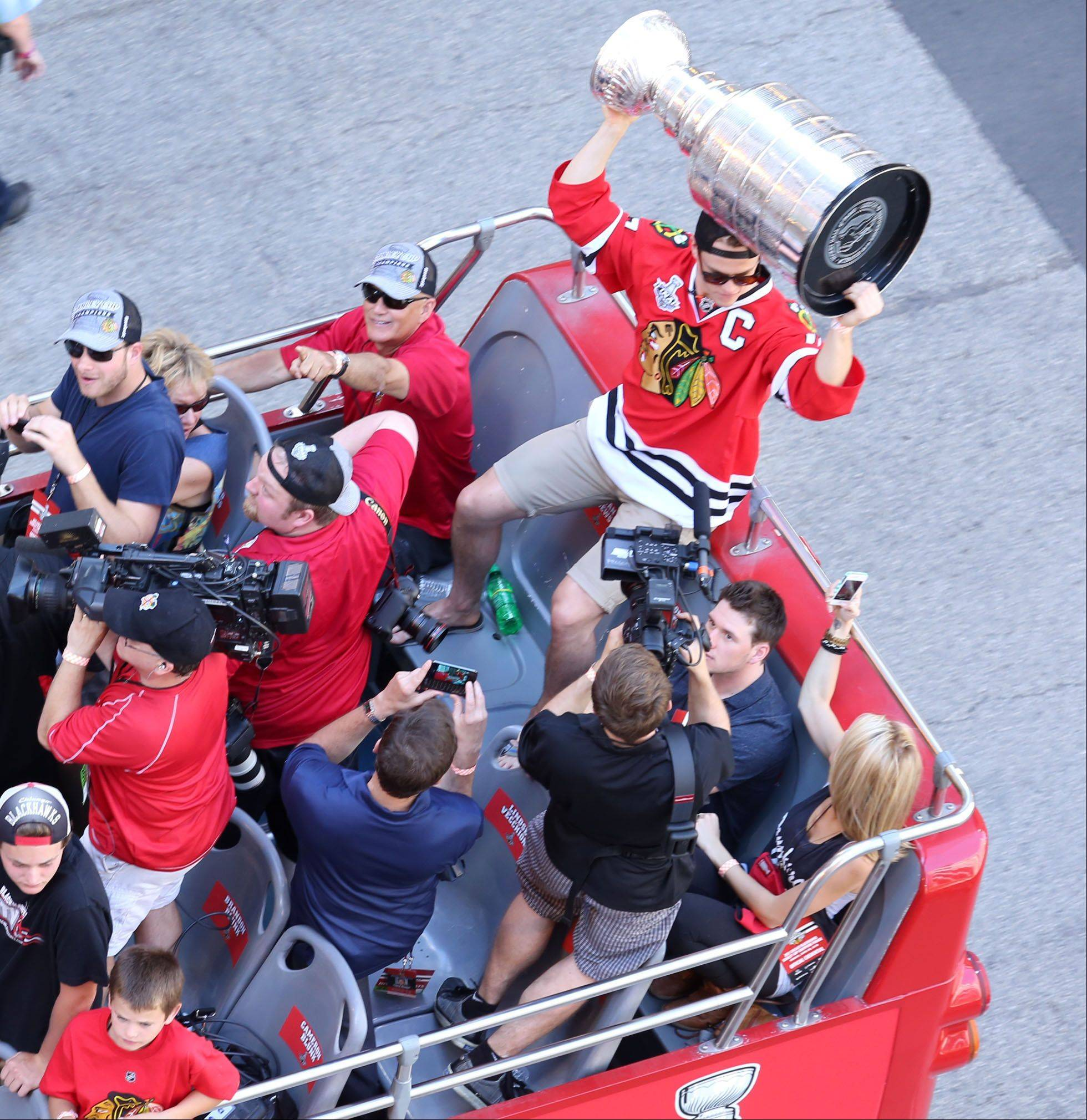 The lead double-decker bus with the Stanley Cup and Blackhawks players travels east on Washington Street to Michigan Avenue in Chicago on Friday.