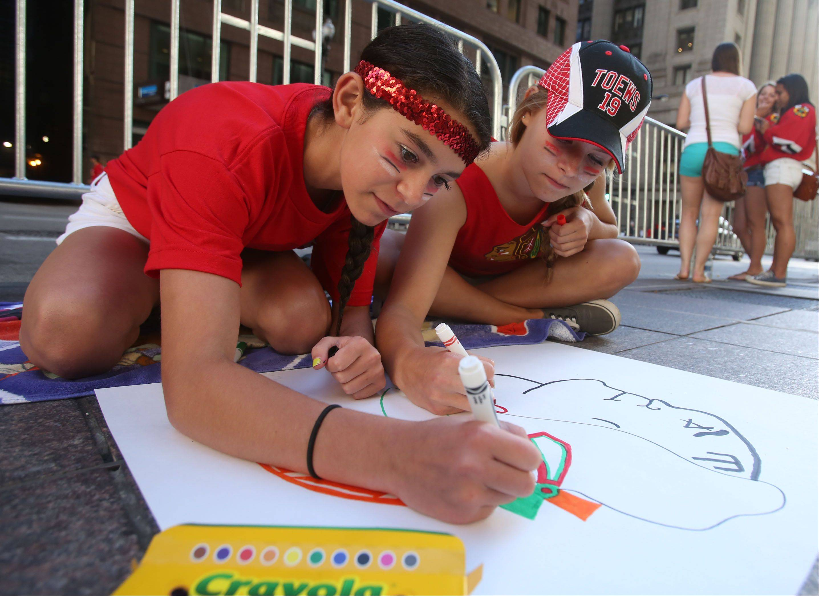 Hannah Graff, left, and Martina Schneider, both 13, of Mount Prospect draw a Blackhawks logo to hold up during the parade in Chicago on Friday.