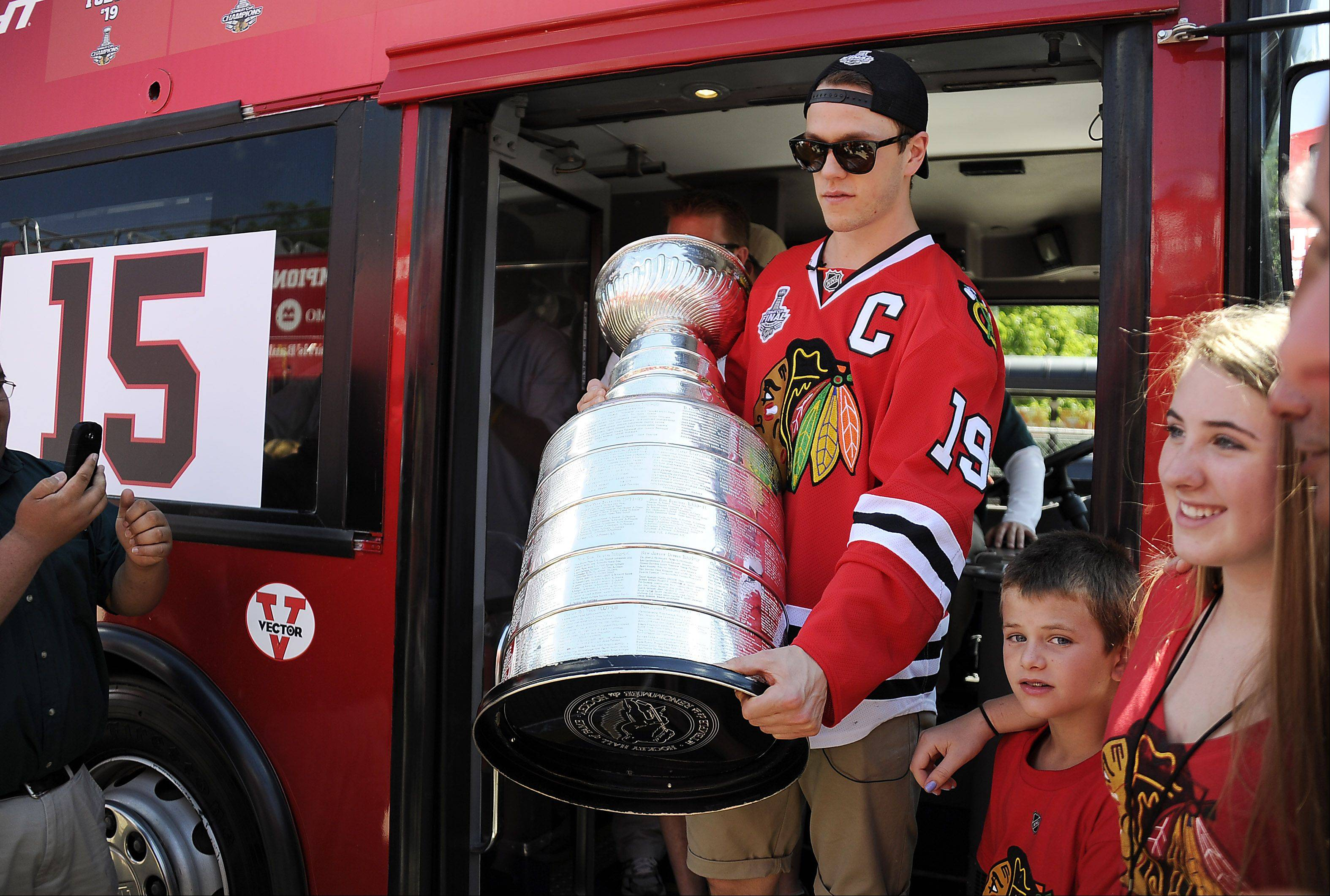 Chicago Blackhawks captain Jonathan Toews carries the Stanley Cup from the players bus as they prepare to show it to Blackhawks fans at Grant Park in Chicago.