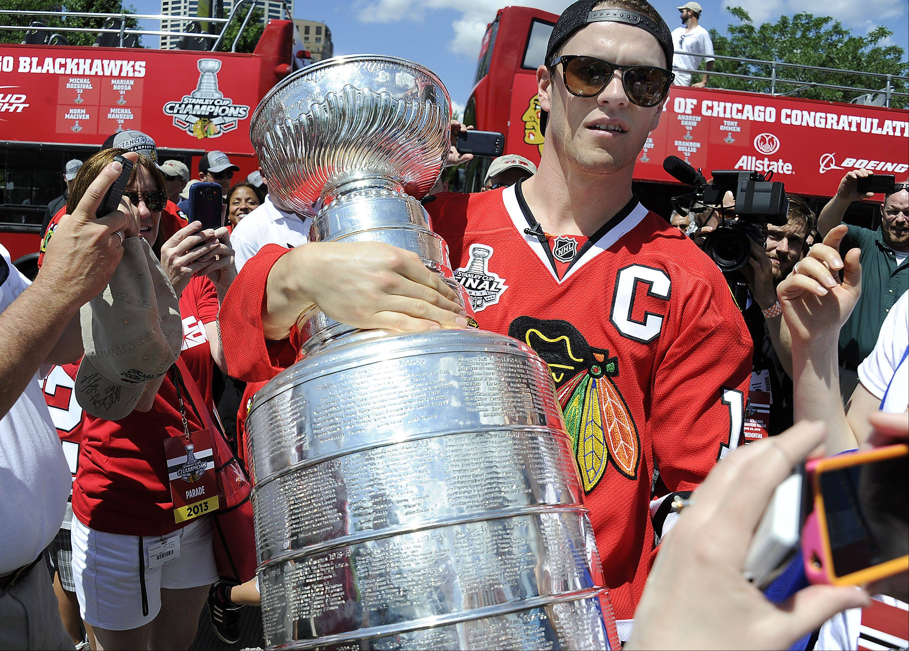 Chicago Blackhawks captain Jonathan Toews carries off the Stanley Cup from the players bus as they prepare to show Blackhawks fans at Grant Park in Chicago.