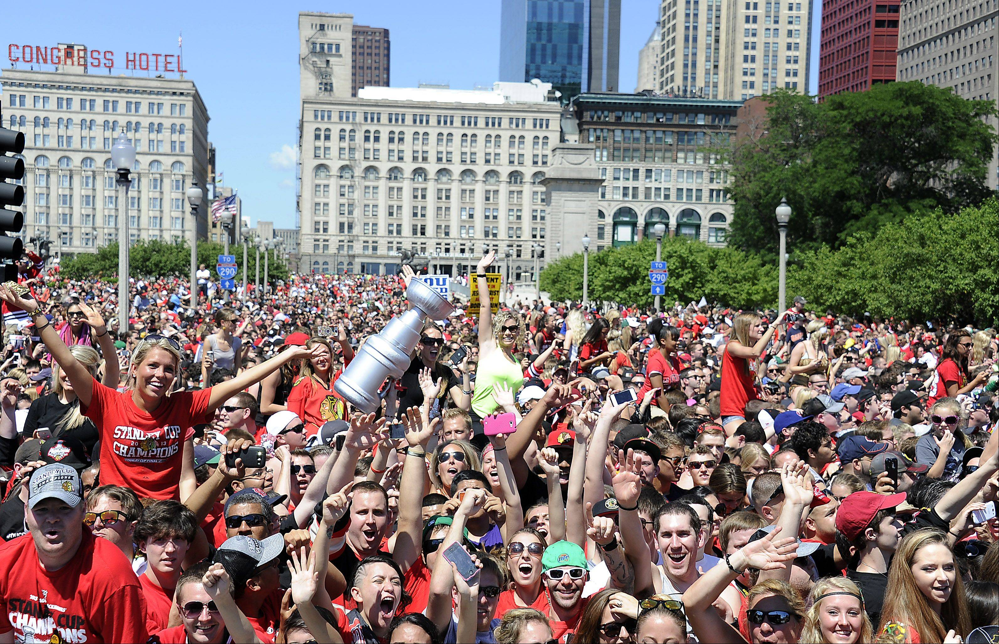 Thousands of Chicago Blackhawks fans crowd along the parade route as they watch the players head toward Grant Park to start the celebration.