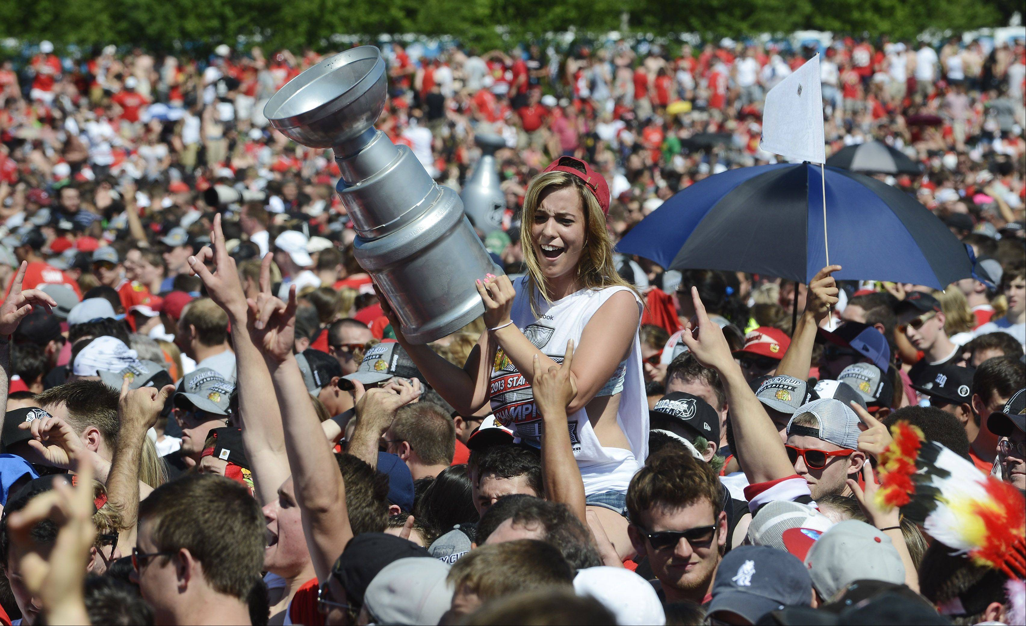 A fan holds up a replica of the Stanley Cup during the Chicago Blackhawks Stanley Cup Rally at Hutchinson Field Friday.