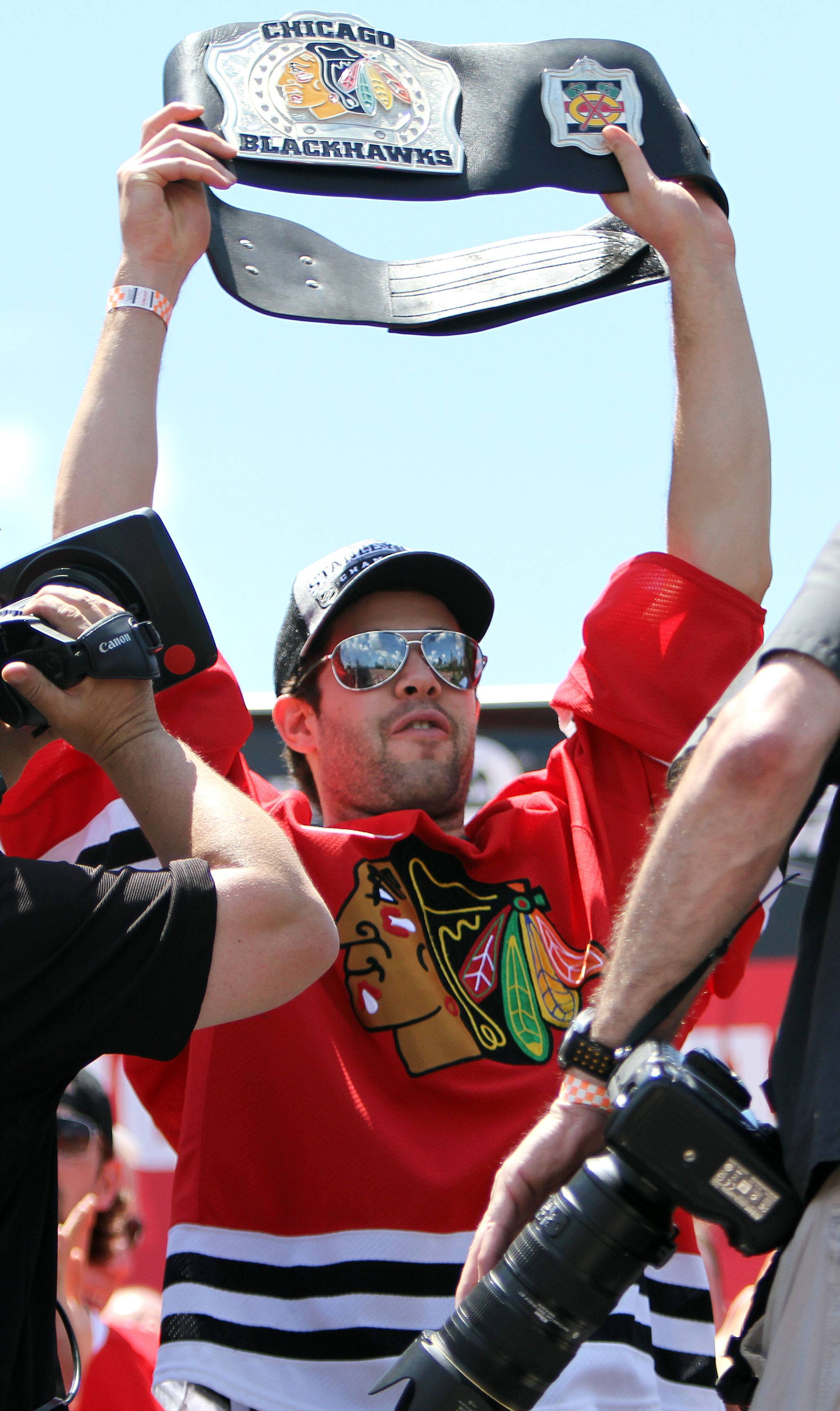 Corey Crawford raises up a wrestling belt given to him by Patrick Kane.