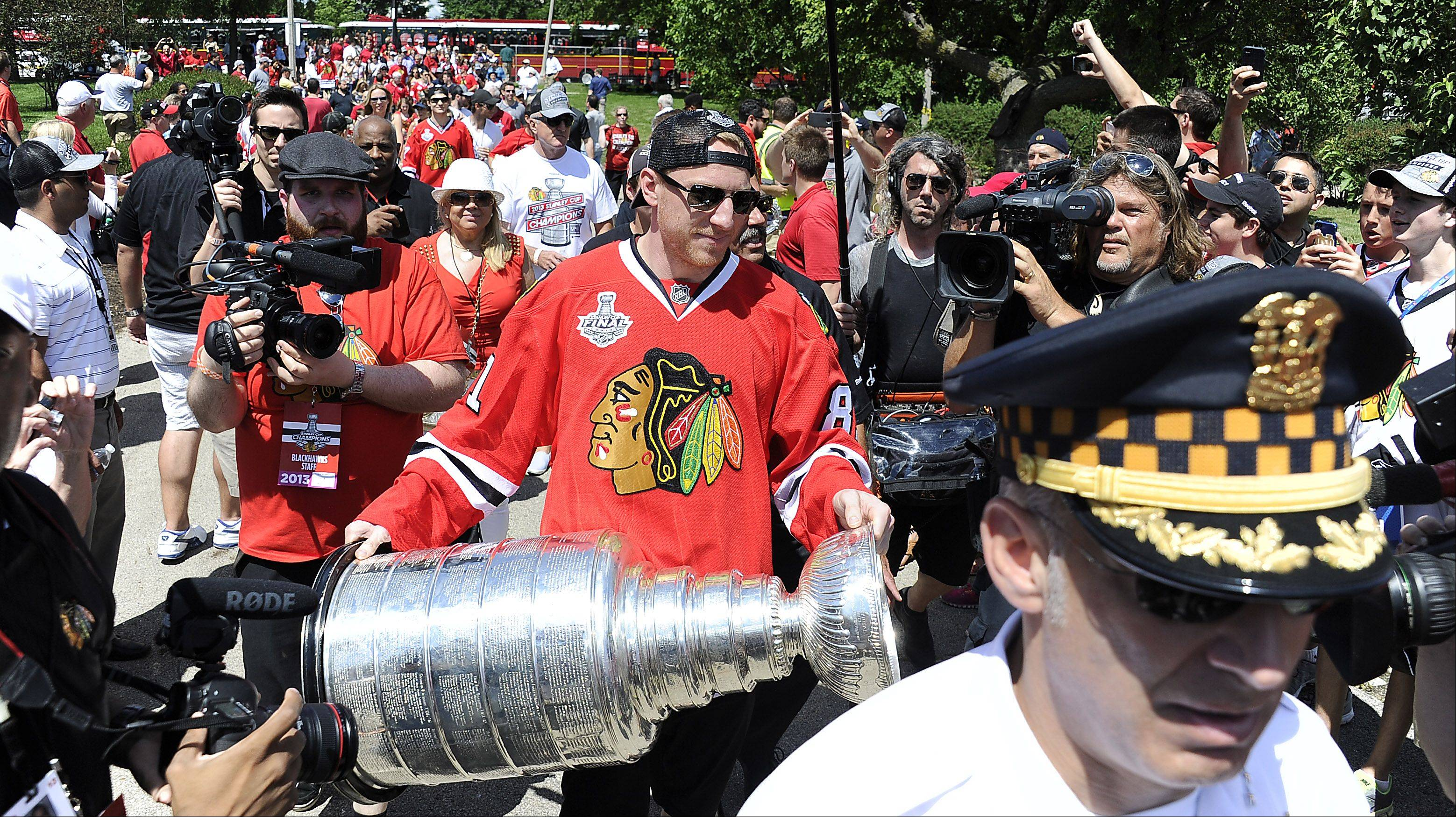 Chicago Blackhawks player Marian Hossa carries the Stanley Cup from the players bus as they prepare to show it to the Blackhawks fans at Grant Park in Chicago.
