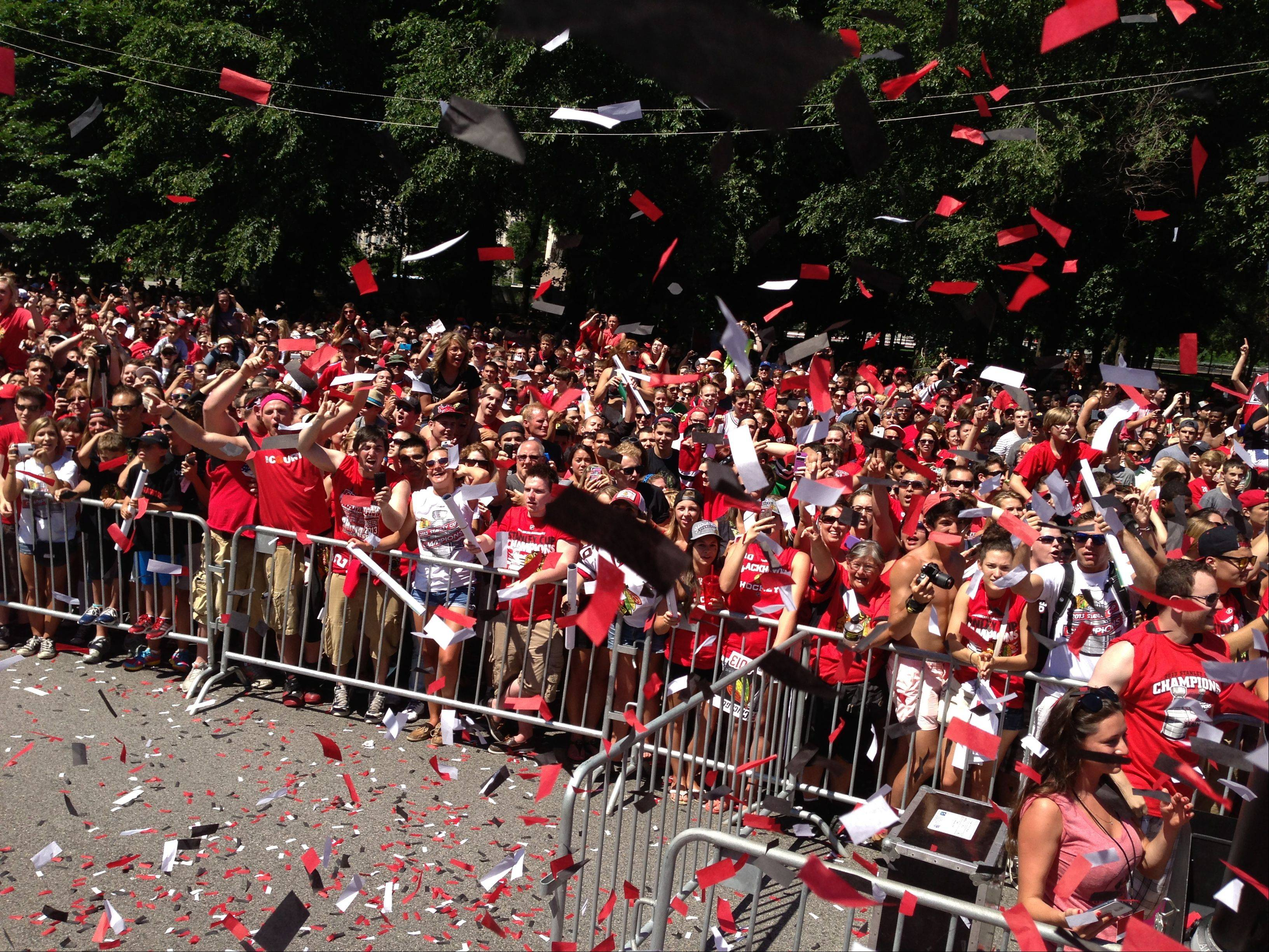 Fans along the parade route cheer on the Chicago Blackhawks as they head to the rally in Grant Park.