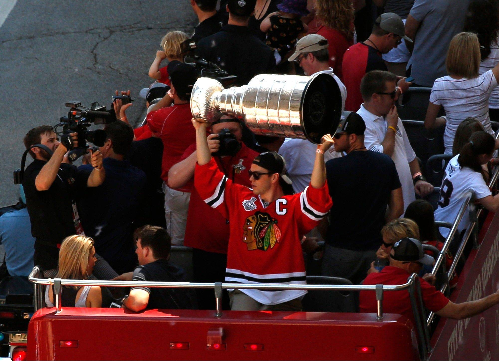 Chicago Blackhawks' Jonathan Toews holds up the 2013 Stanley Cup during a victory parade down Washington Street Friday, June 28, 2013 in Chicago. The Blackhawks celebrate the team's second championship in four years.