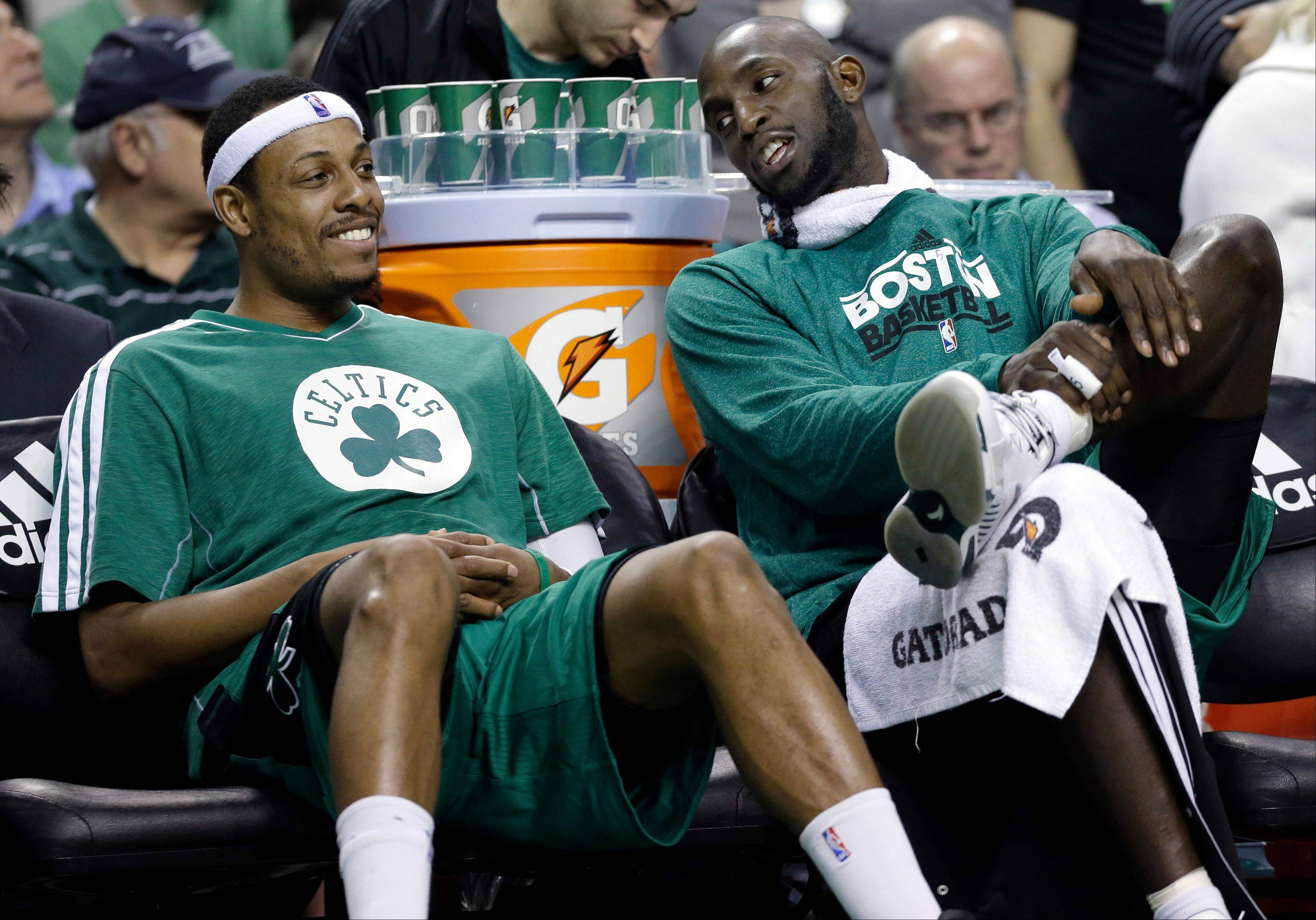 FILE - Boston Celtics center Kevin Garnett, right, chats with teammate Paul Pierce on the bench during the fourth quarter of an NBA basketball game against the Toronto Raptors in Boston, in this March 13, 2013 file photo. The Brooklyn Nets will acquire Paul Pierce and Kevin Garnett from the Boston Celtics in a deal that was still developing as the NBA draft ended, according to a person with knowledge of the details. The trade can't be completed until July 10, after next season's salary cap is set, so pieces were still being discussed early Friday June 28, 2013.