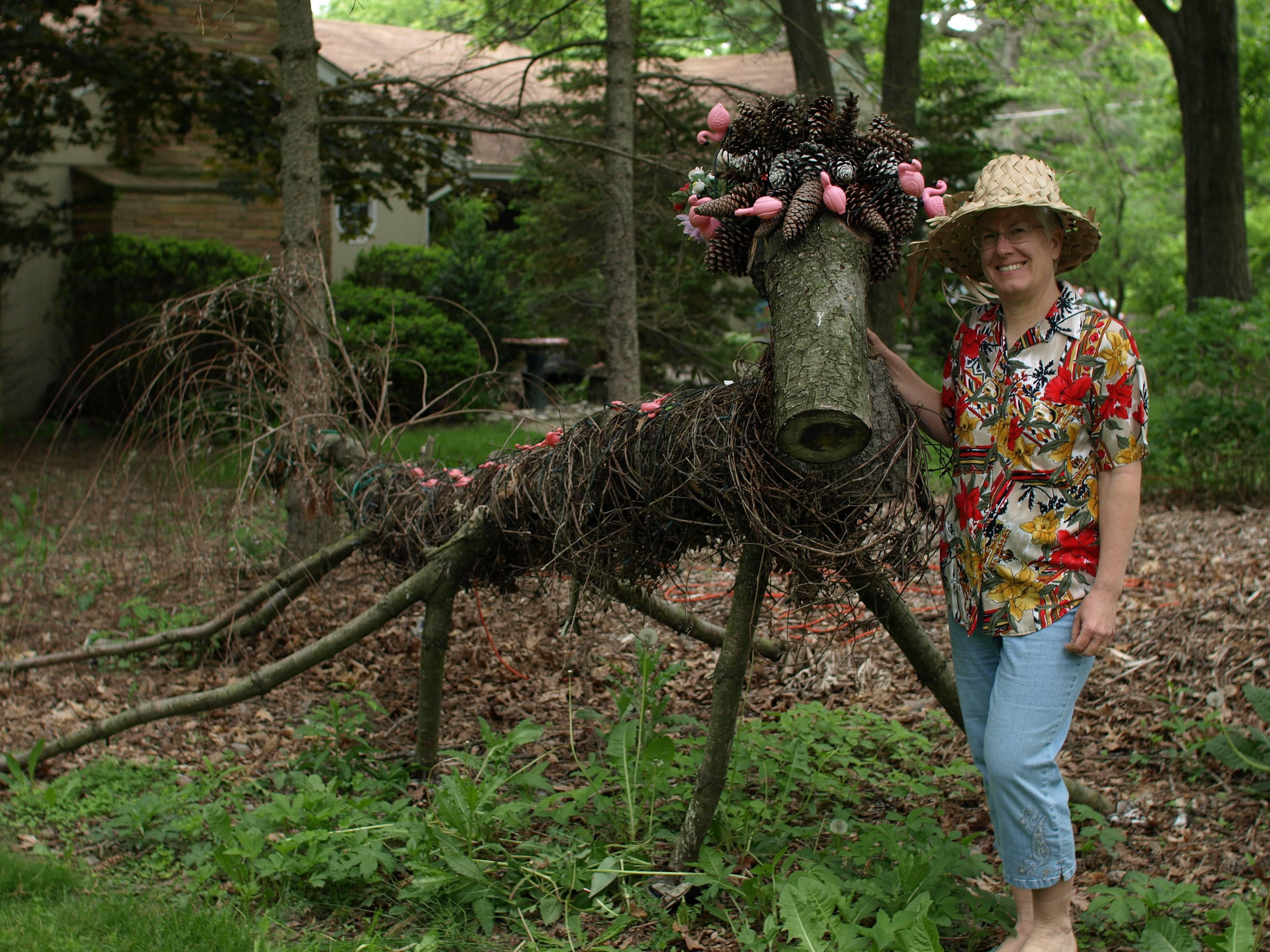 "When Mother Nature blew the top off of a large pine tree, artist Kathy Steere created ""Gus, the Guardian of the Storm"" in 2012.  After sporting a red and green scarf for the winter, Gus is currently garbed in pink flamingos."
