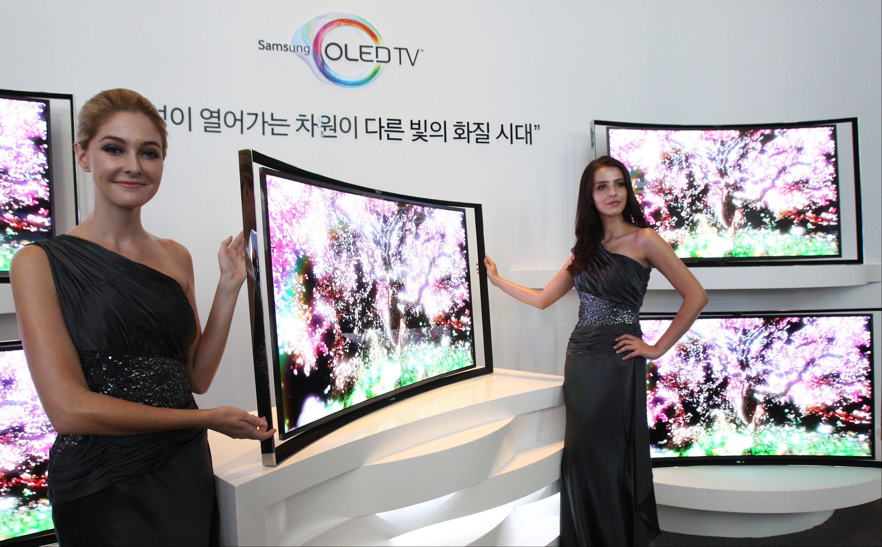 Models pose Thursday with a Samsung Electronics Co.�s 55-inch curved OLED TV during a news conference at its headquarters in Seoul, South Korea. After delays, Samsung rolled out Thursday the curved TV that uses an advanced display called OLED. The 55-inch TV will sell for $13,000 in South Korea, more than five times the cost of LCD televisions of the same size.