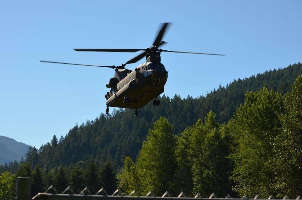 An Oregon National Guard Chinook helicopter heads up to Oregon's Mount Hood Friday in the search for 59-year-old Salem, Ore., dentist Kinley Adams.