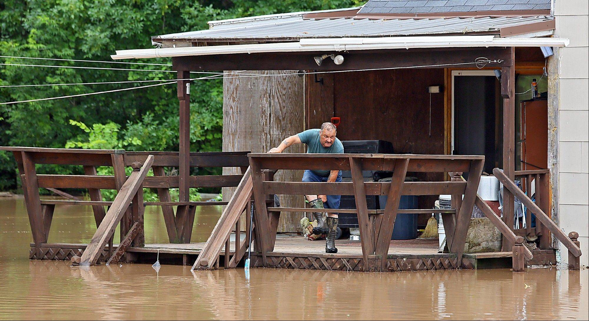 Dave Pearo takes water out of his boots Friday at his home by the Onieda River, in Oneida, N.Y.