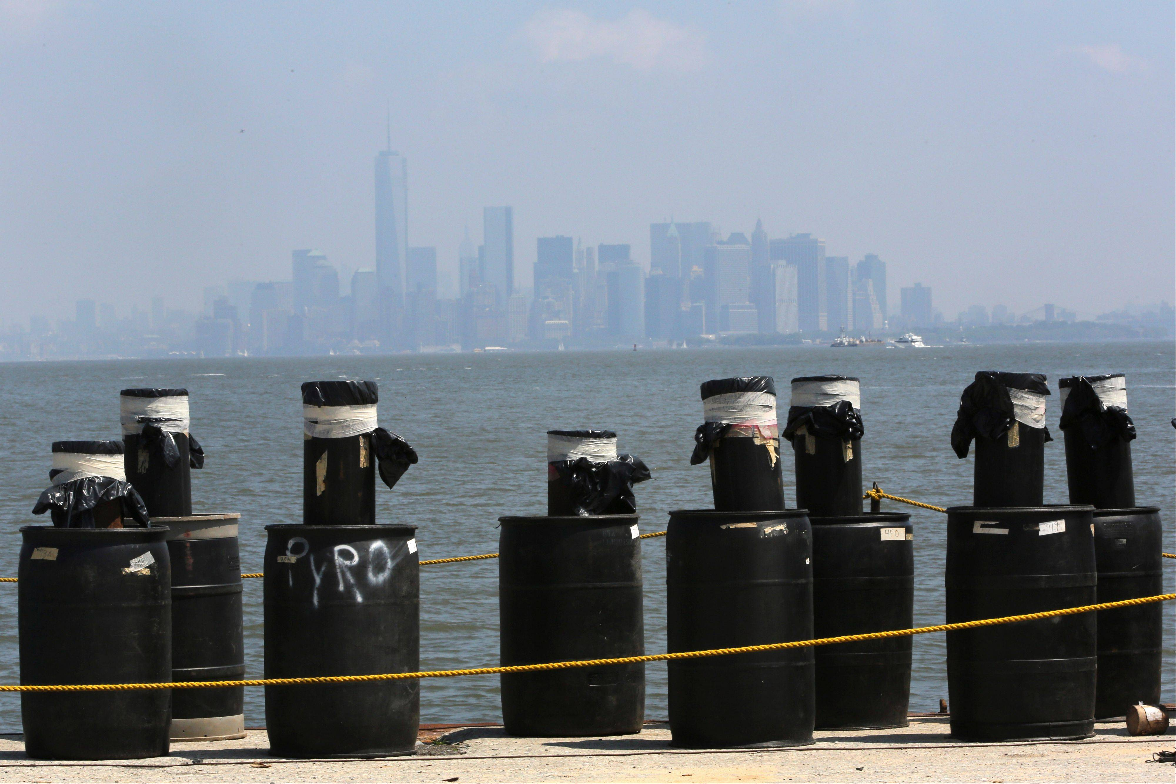 Mortars placed on a barge docked in the Staten Island borough of New York are in front of the hazy lower Manhattan skyline on Saturday,