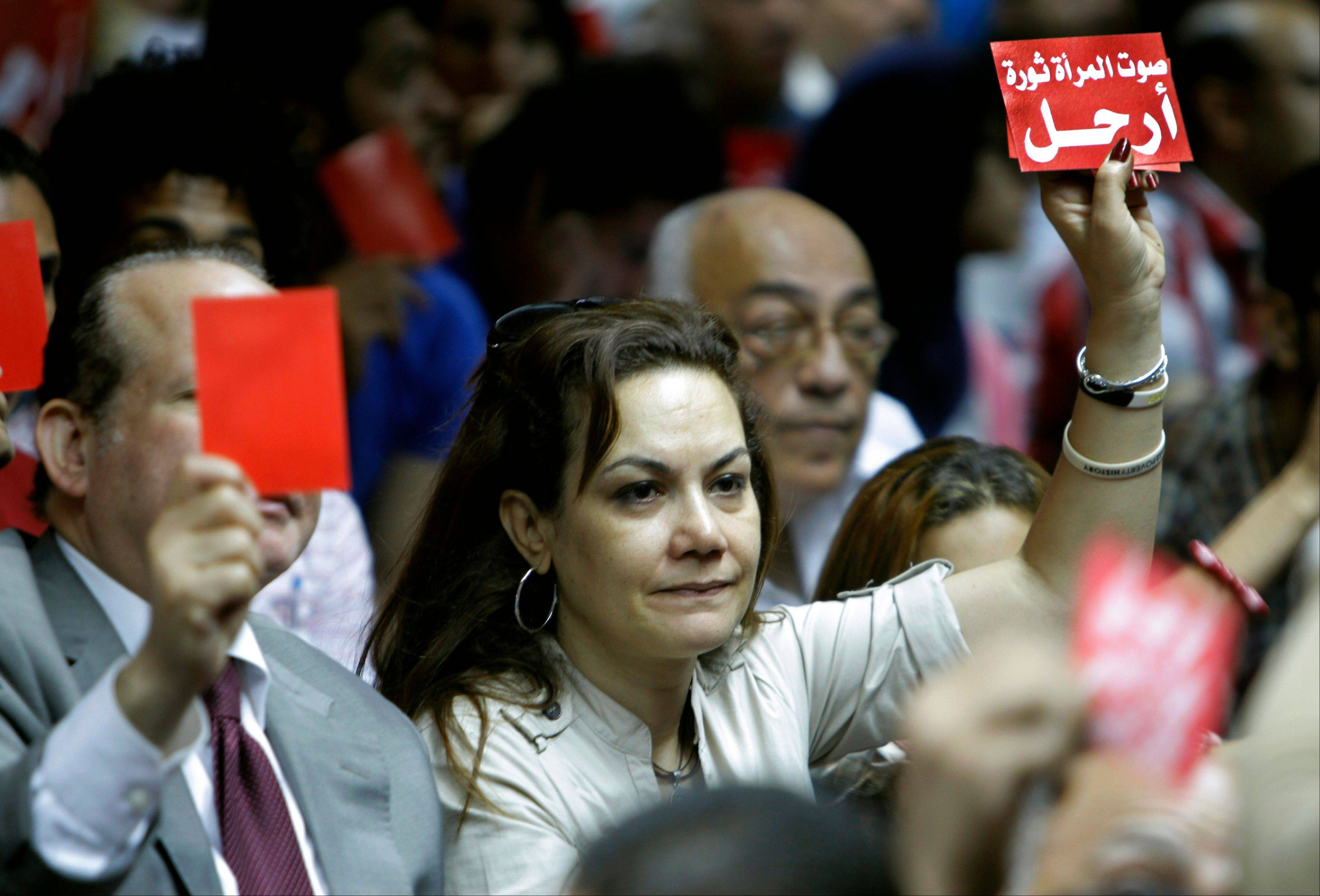 "Bothaina Kamel, Egypt's first female presidential candidate who ran against President Mohammed Morsi during the 2012 presidential race, raises a red card with Arabic reads, ""leave"", during a press conference Saturday of the Tamarod campaign, Arabic for ""Rebel"", calling for the ouster of Morsi in Cairo."