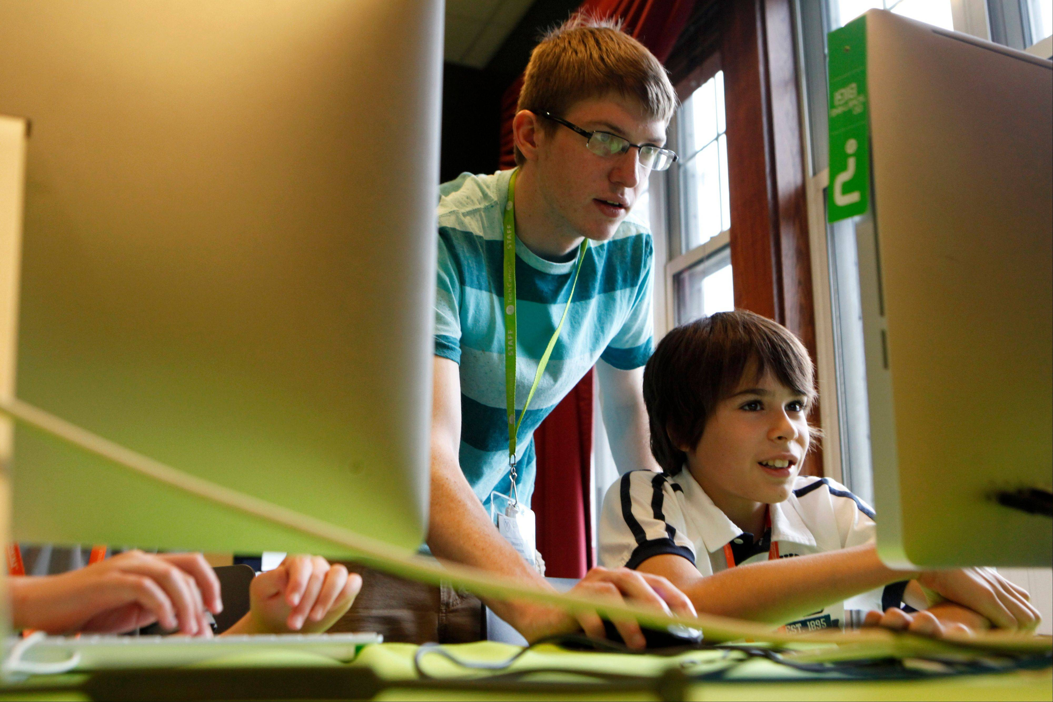 Instructor Thaddeus Owings, left, helps camper Nicholas Sanchez work on creating a video game while at an iD Tech Camp at the Emory University campus in Atlanta. So-called coding camps for kids are becoming more popular amid a growing effort to expand access to computer programming and inspire more youths to seek computer science degrees and later careers in technology.