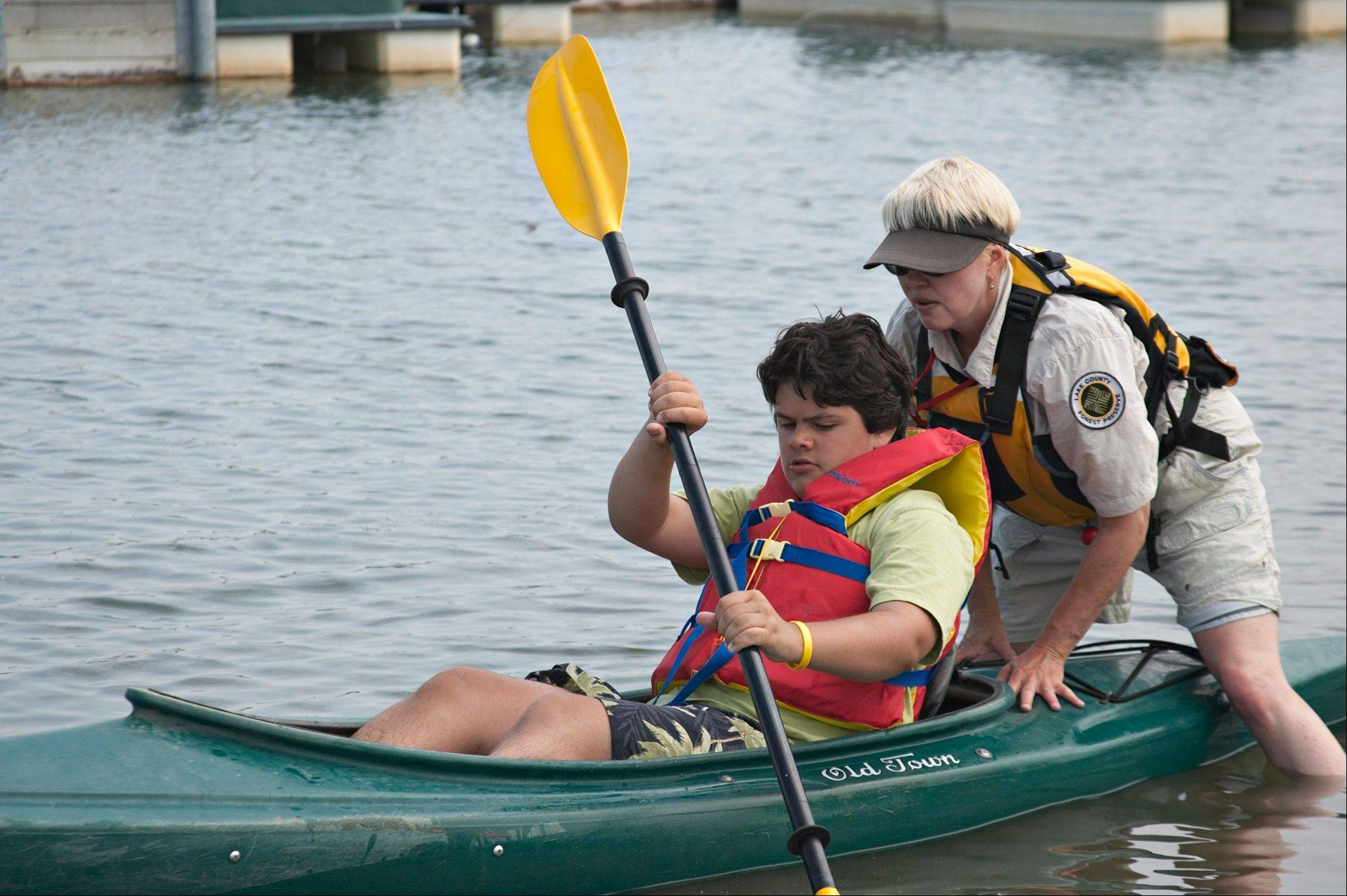 Paddling Camp instructor Jan Ward helps a student at Independence Grove through the Lake County Forest Preserve.