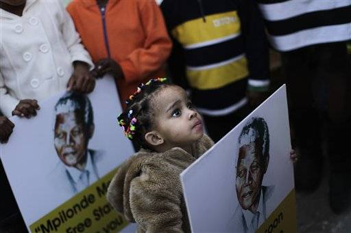 A South African girl holds a poster showing former South African President Nelson Mandela, while her family and other well wishers gather at the entrance to the Mediclinic Heart Hospital where former South African President Nelson Mandela is being treated in Pretoria, South Africa Friday, June 28, 2013. Members of Nelson Mandela's family as well as South African Cabinet ministers have visited the hospital on Friday where the 94-year-old former president is critically ill.
