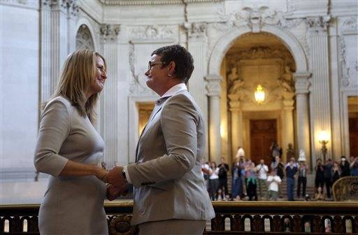 Sandy Stier, left, exchanges wedding vows with Kris Perry during a ceremony presided by California Attorney General Kamala Harris at City Hall in San Francisco, Friday, June 28, 2013. Stier and Perry, the lead plaintiffs in the U.S. Supreme Court case that overturned California's same-sex marriage ban, tied the knot about an hour after a federal appeals court freed same-sex couples to obtain marriage licenses for the first time in 4 1/2 years.