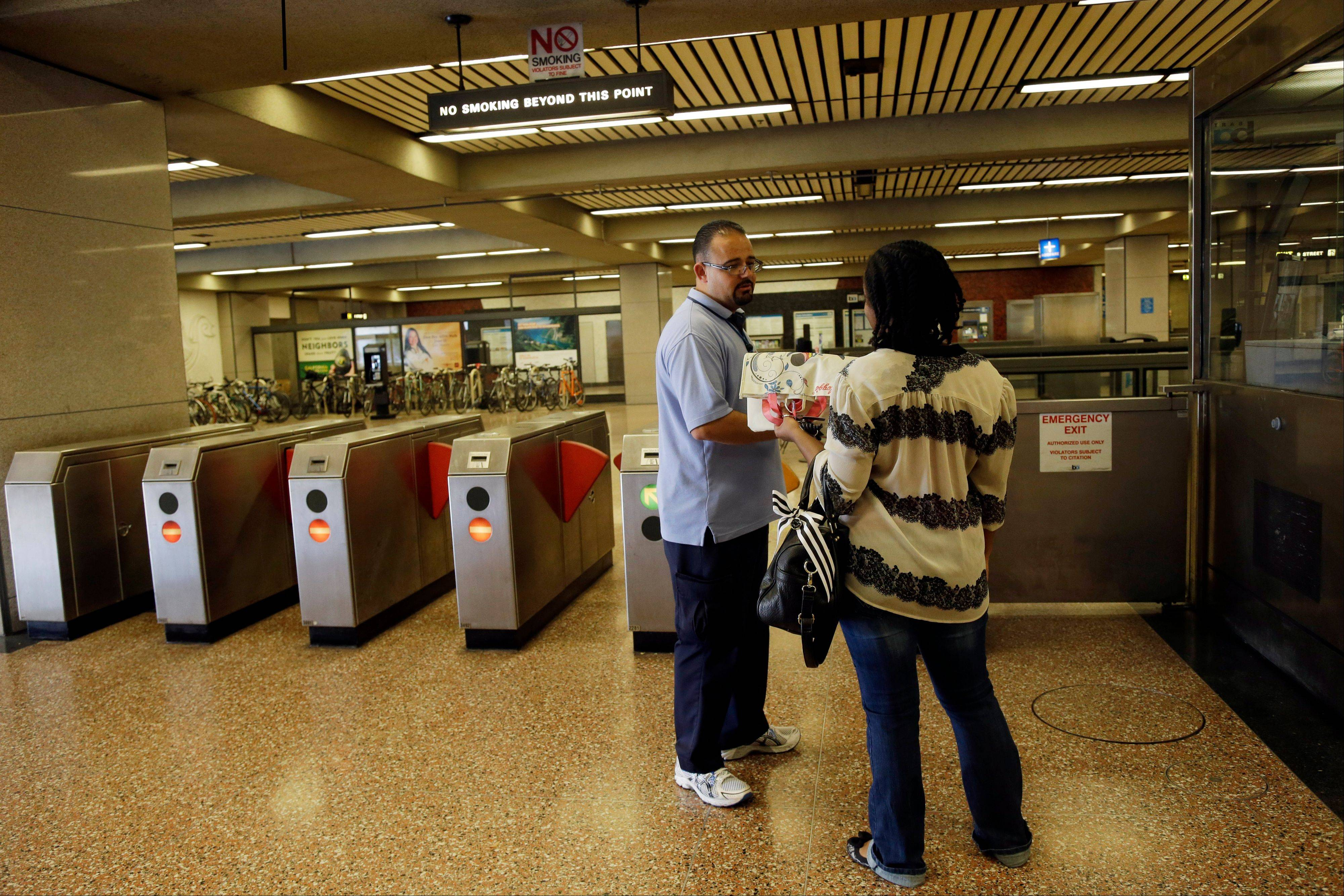 BART station agent Mark Madrigal helps a customer Friday at the Lake Merritt station in Oakland, Calif.