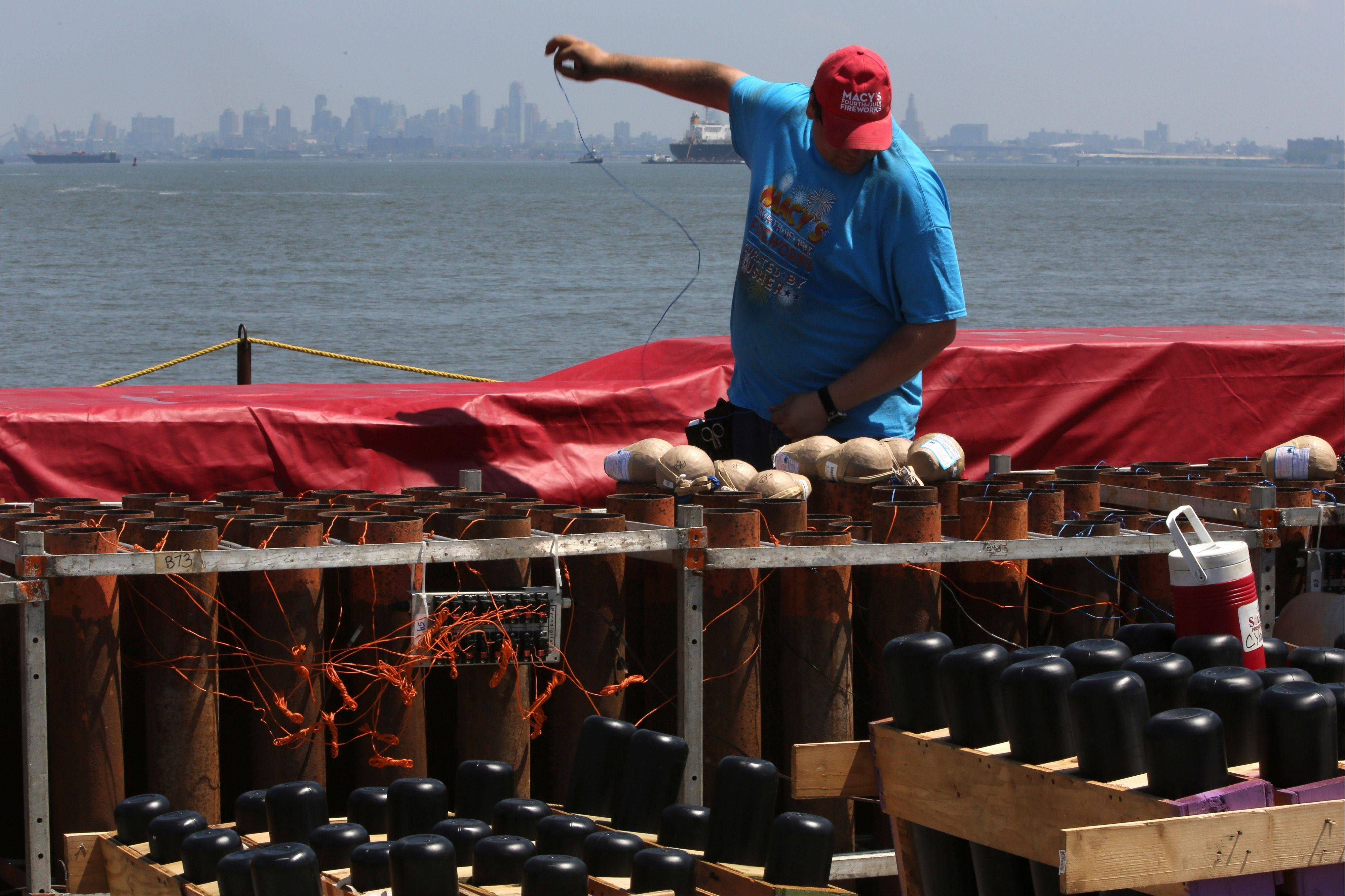 A worker loads shells into mortars on a barge docked Saturday in the Staten Island borough of New York.