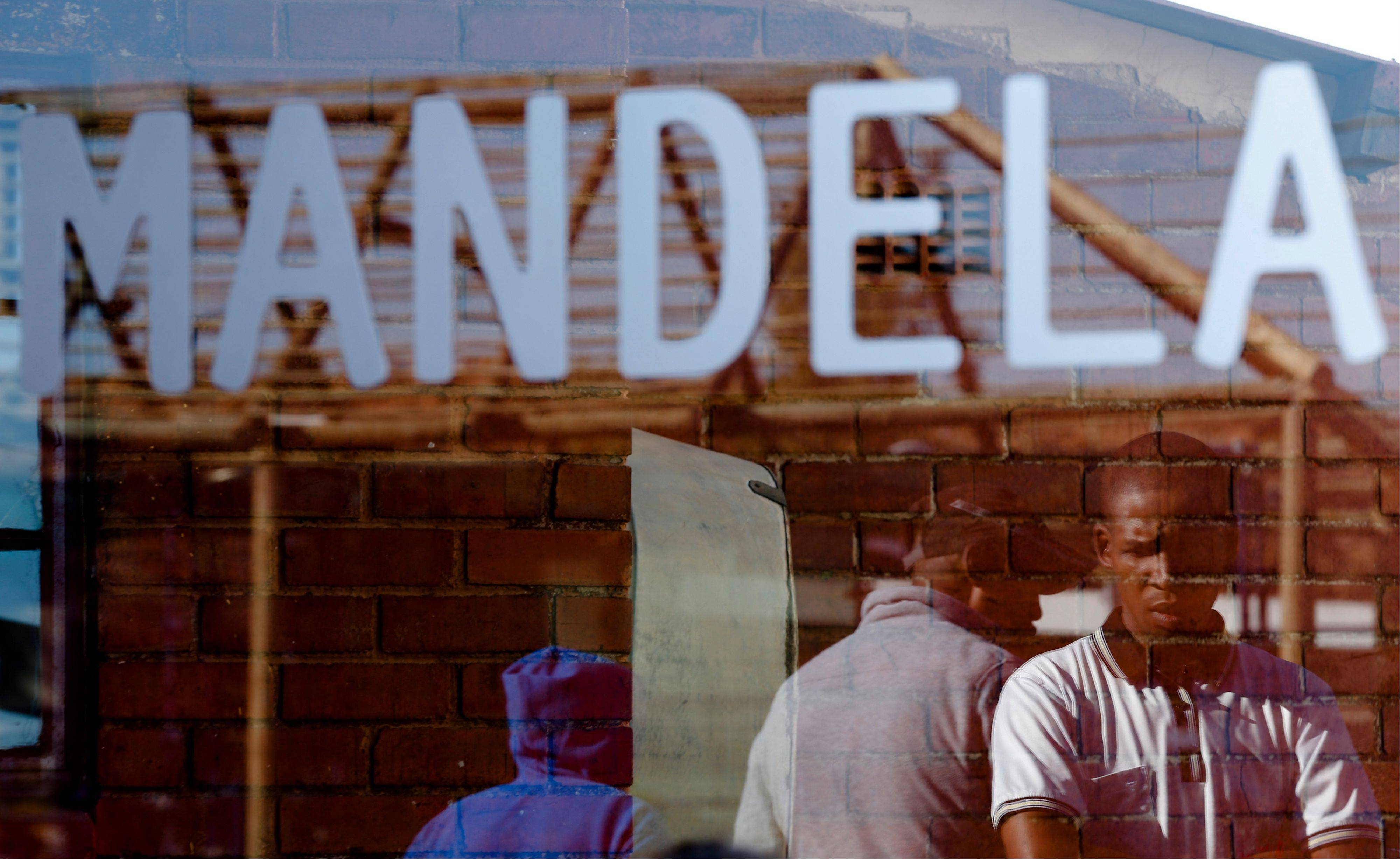 People are reflected in a window Thursday of the house of former South African President Nelson Mandela in Soweto.