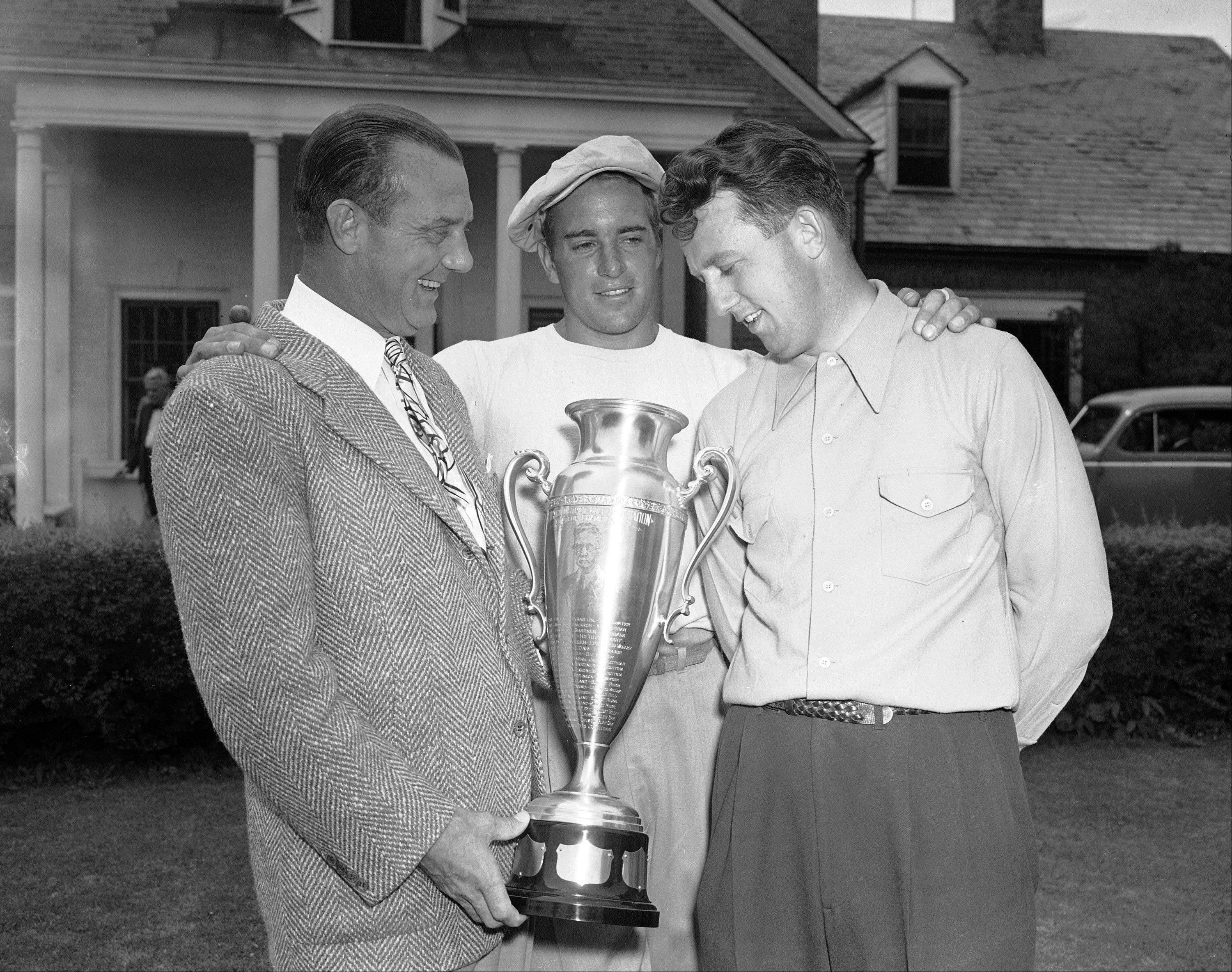 Golfer Ray Billows, right, winner of the first Great Lakes amateur golf championship, receives the tournament trophy from Scotty Fessenden, left, president of the Chicago District Golf Association, as Frank Stranahan, center, looks on.