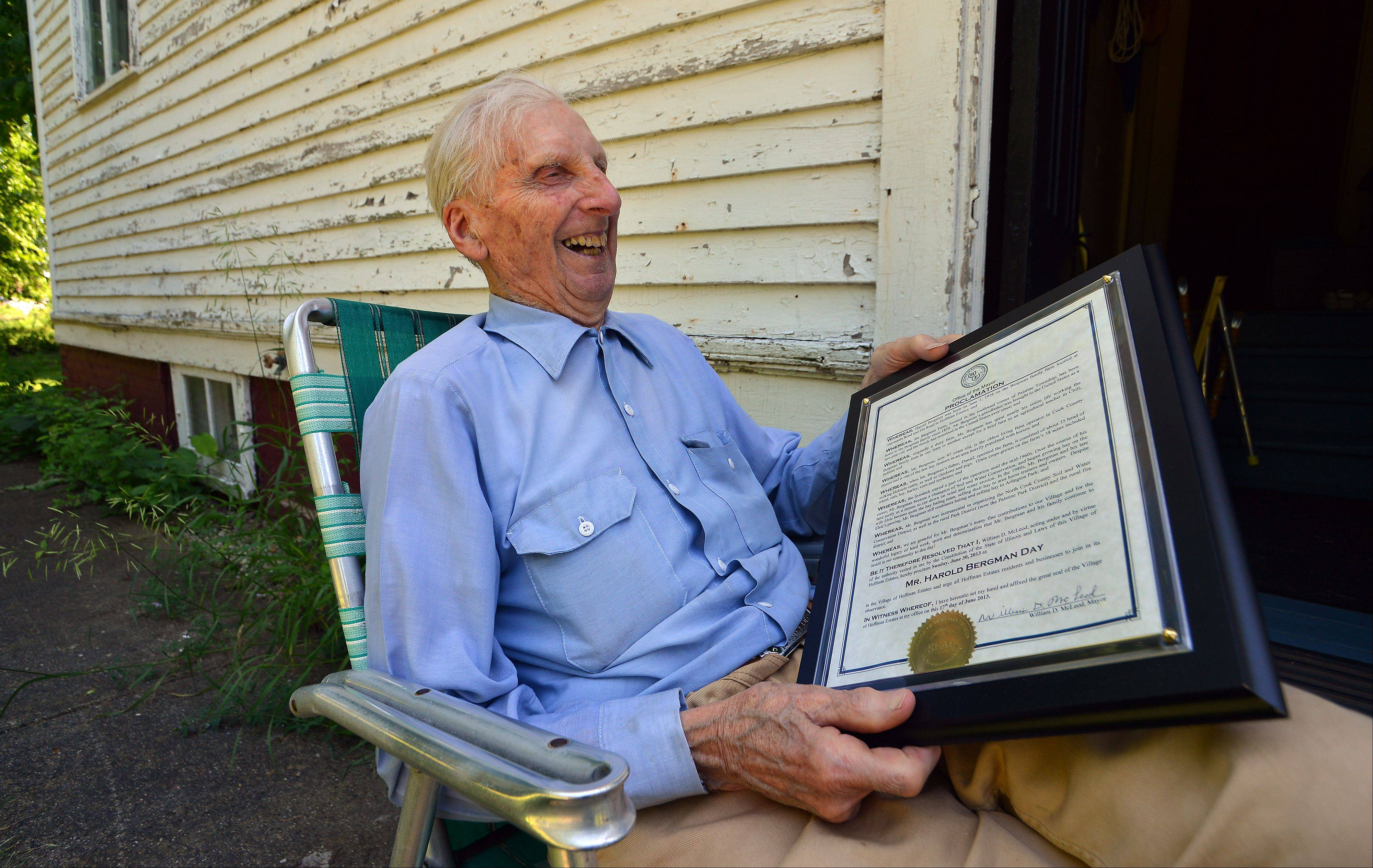 Harold Bergman, 97, of Hoffman Estates sits in his backyard next to the house he was born in smiling as he looks over the proclamation declaring today Harold G. Bergman Day.