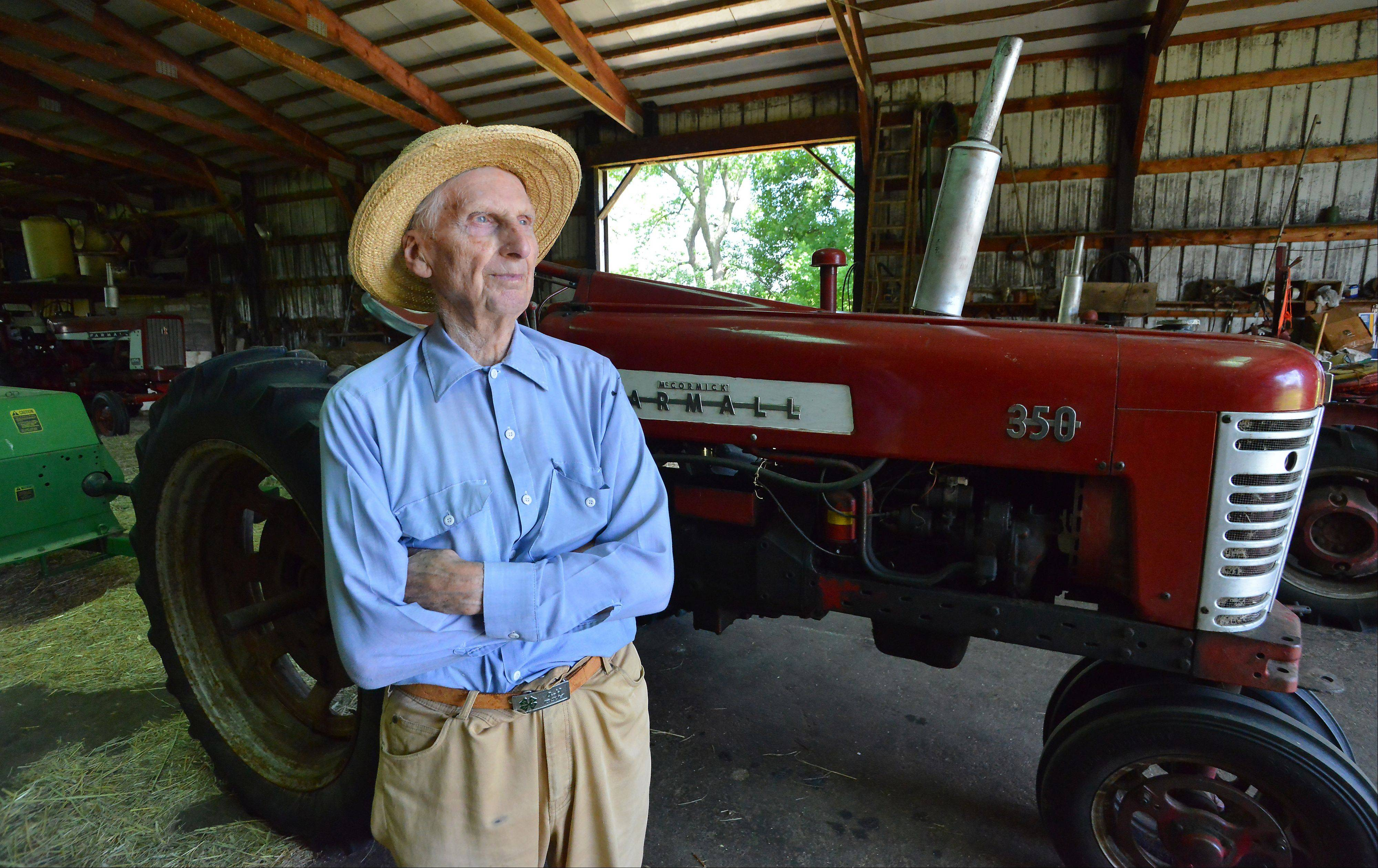 Harold Bergman, 97, of Hoffman Estates talks about being the oldest farmer in Cook County in his barn next to the tractor he still uses to bale hay.
