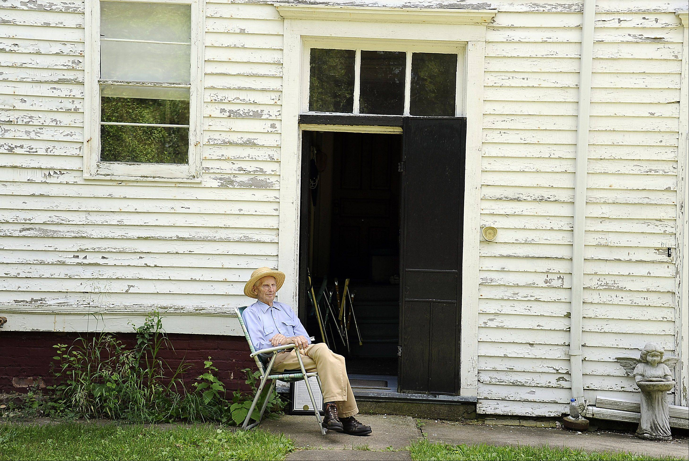 Harold Bergman, 97, of Hoffman Estates sits in his backyard next to the house he was born in, soaking up the cool air filtering up from the cellar on a hot summer day.