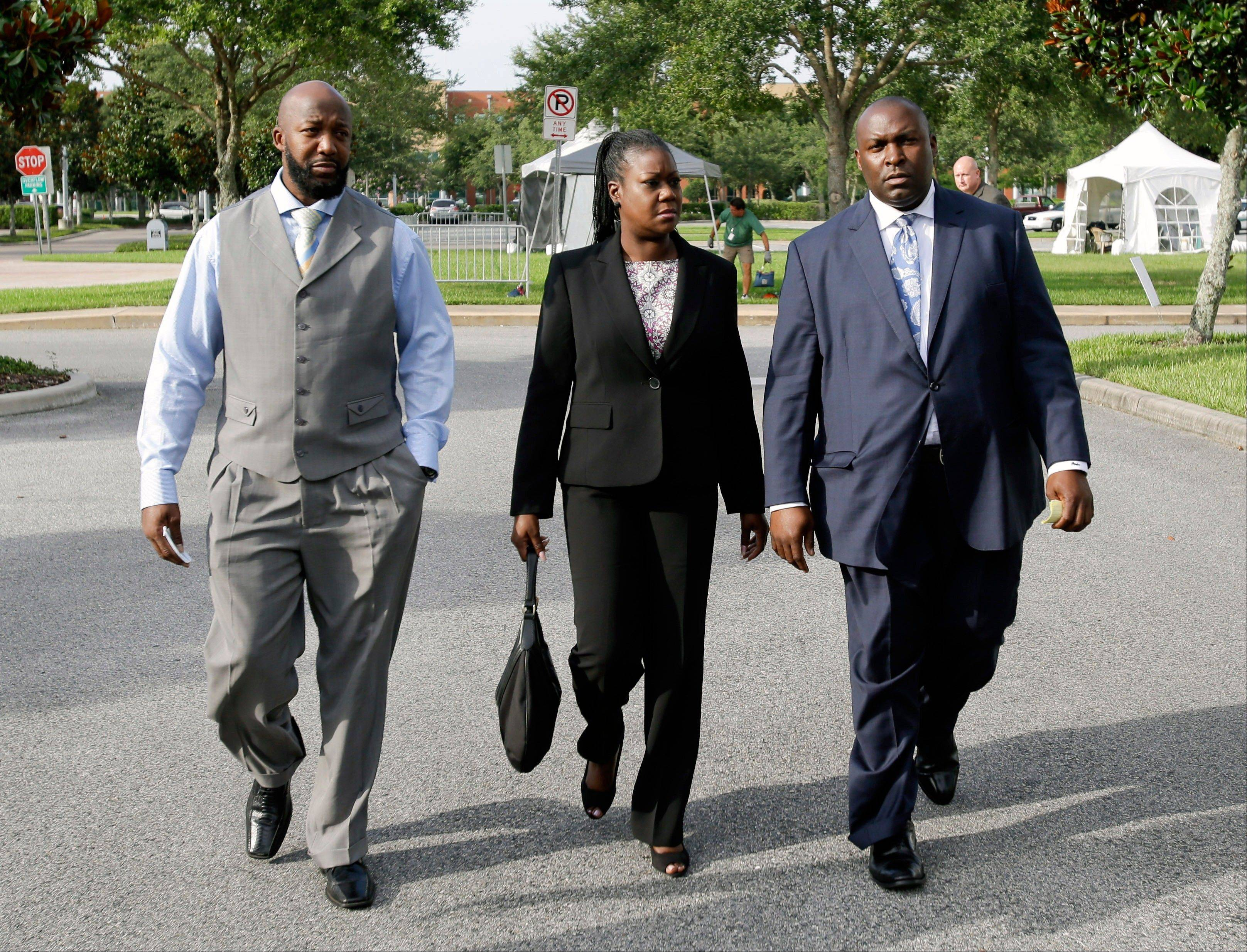Tracy Martin, left, and Sybrina Fulton, center, parents of slain teen Trayvon Martin, leave the Seminole County Courthouse Thursday with their attorney Daryl Parks at the end of the day's proceedings in the trial of George Zimmerman, in Sanford, Fla.
