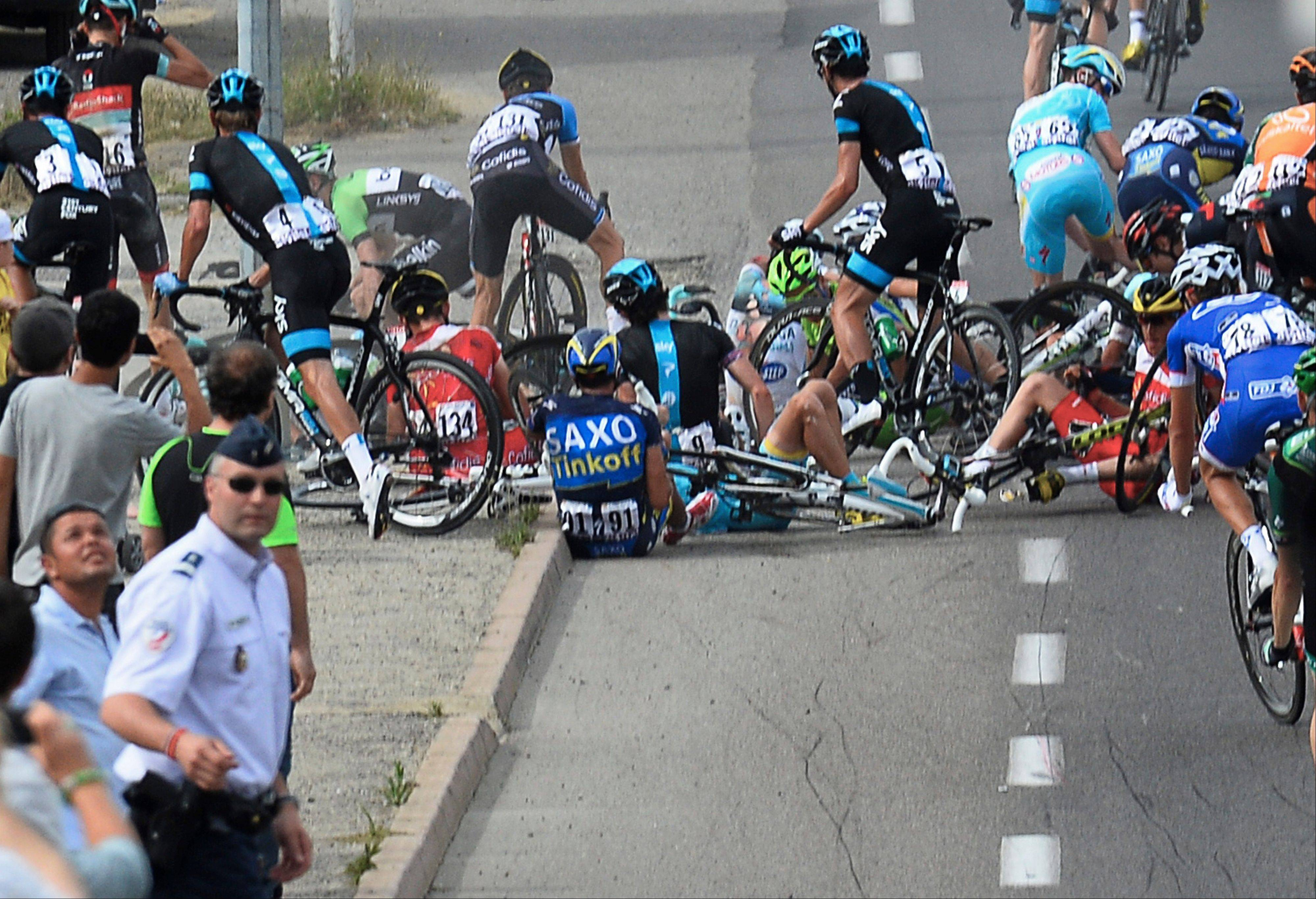 Alberto Contador of Spain, center with number 91, sits on the road after a group of riders crashed during the first stage of the Tour de France cycling race over 213 kilometers (133 miles) with start in Porto Vecchio and finish in Bastia, Corsica island, France, Saturday June 29, 2013.
