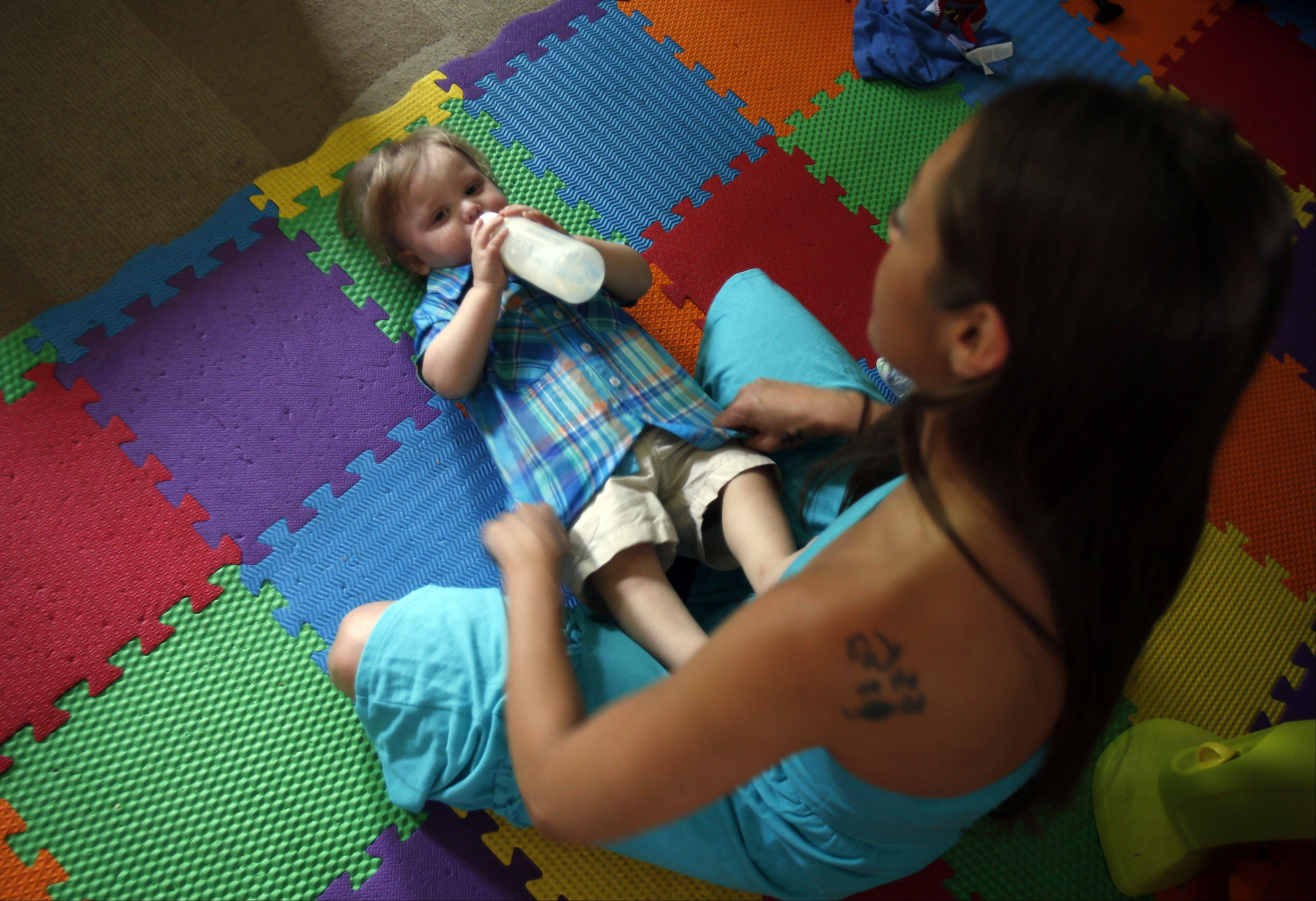 Hollie Redinger of Elgin gets her son, Mason, 18 months, ready. Redinger is part of a group of parents that have decided to forgo vaccinations.