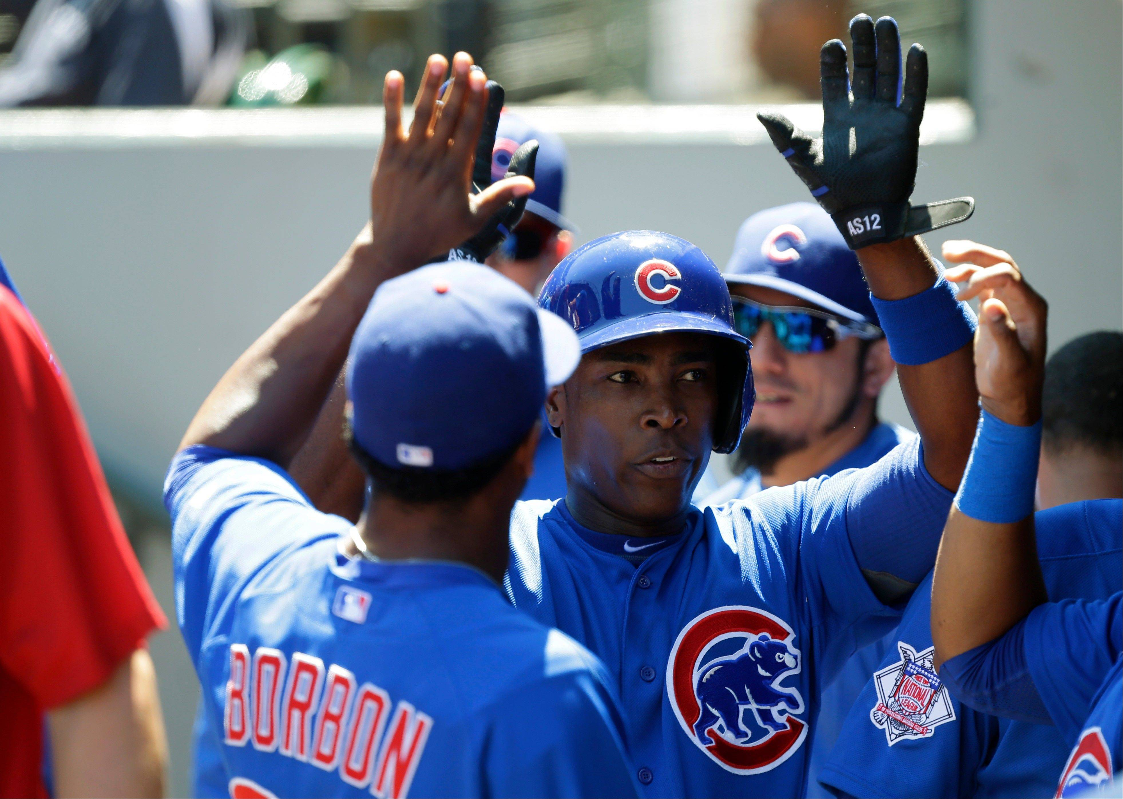 Chicago Cubs' Alfonso Soriano is greeted in the dugout after he scored against the Seattle Mariners in the second inning of a baseball game, Sunday, June 30, 2013, in Seattle. (AP Photo/Ted S. Warren)