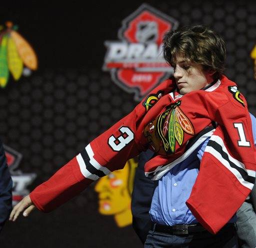 Ryan Hartman, a winger, pulls on a Chicago Blackhawks sweater after being chosen 30th overall in the first round of the NHL hockey draft, Sunday, June 30, 2013, in Newark, N.J. (AP Photo/Bill Kostroun)