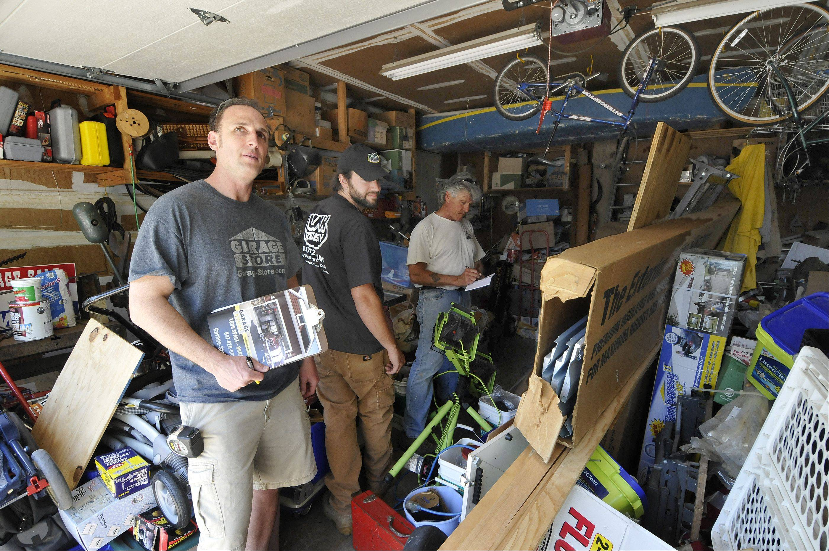 Jim Melchert from Garage Store, left, Nick DeGiulio from Junk Remedy center, and Mel Alger, right, plot their cleanup strategy in the DeBellis' garage.