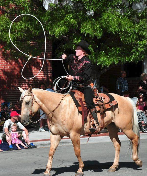 The Grand Parade features several equestrian entries, including a trick roper.