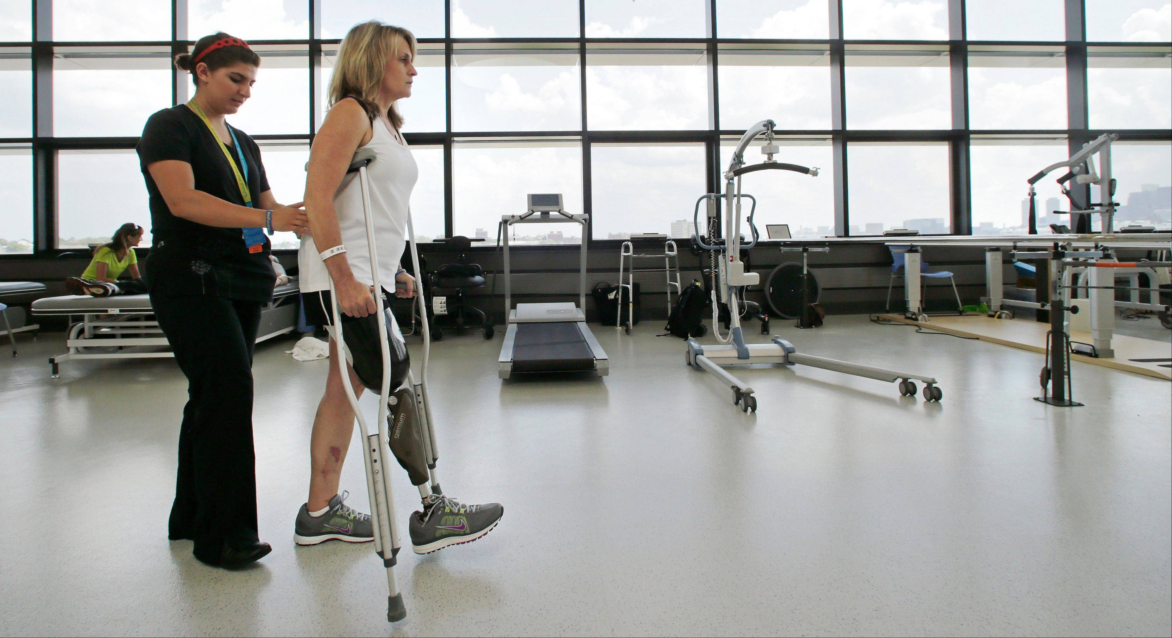 With physical therapist Dara Casparian, left, guiding her strides, Boston Marathon bombing survivor Roseann Sdoia, of Boston, looks forward toward a mirror at the Spaulding Rehabilitation Hospital.