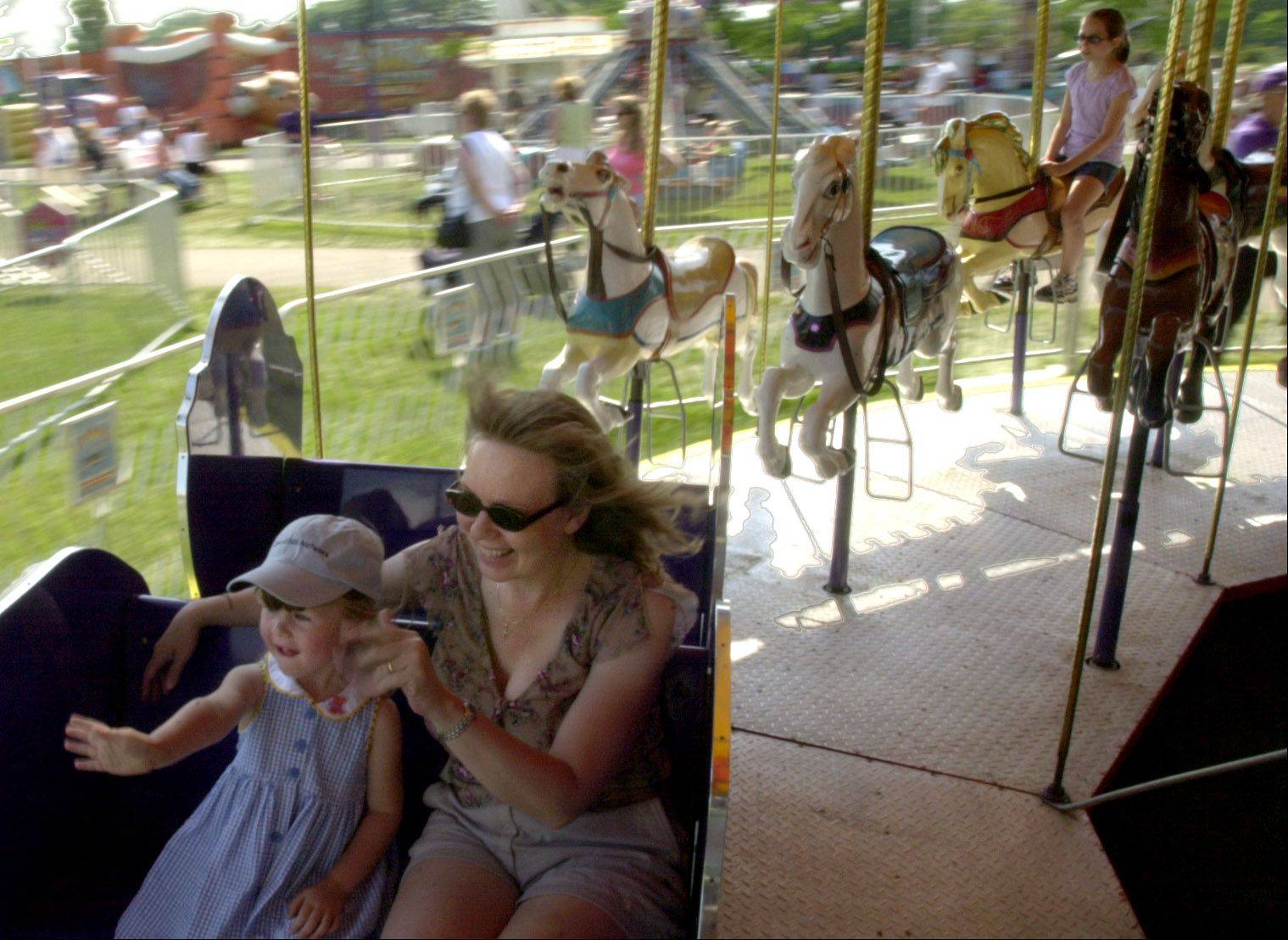 People ride the carousel at Bartlett's Fourth of July Festival at the Apple Orchard Community Park.