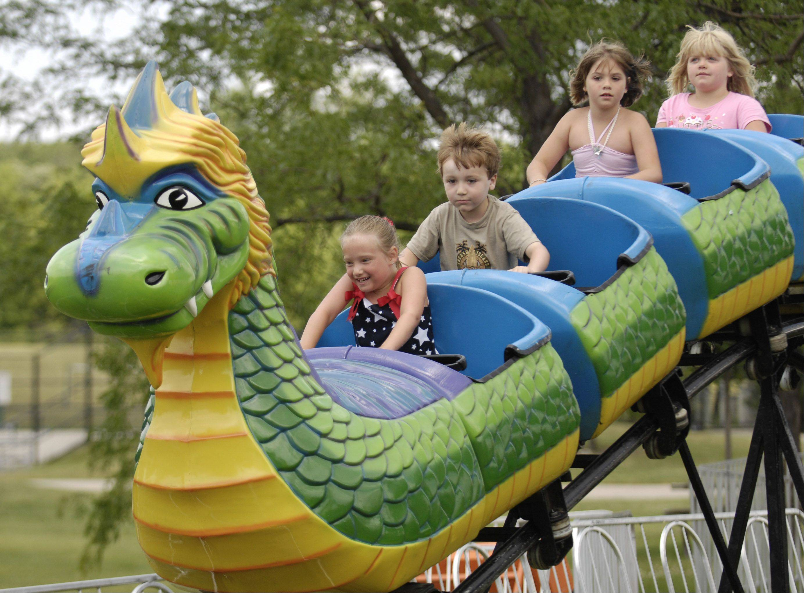 Kids hang on tight while riding a dragon coaster at the Bartlett Fourth of July Festival.