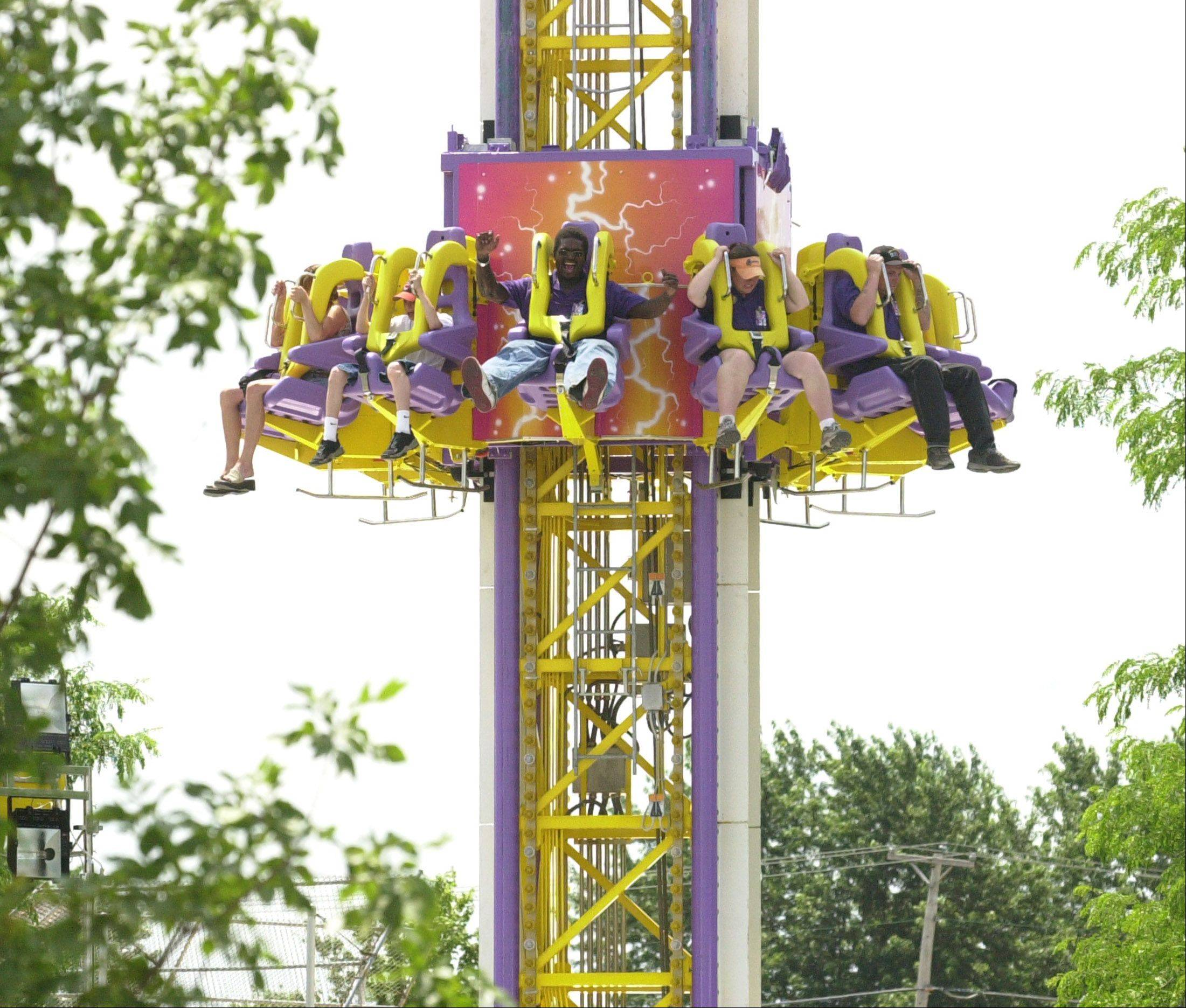 "To the thrill of riders, the ""Mega Drop"" carnival ride plunges toward the ground during the Bartlett Fourth of July Festival."